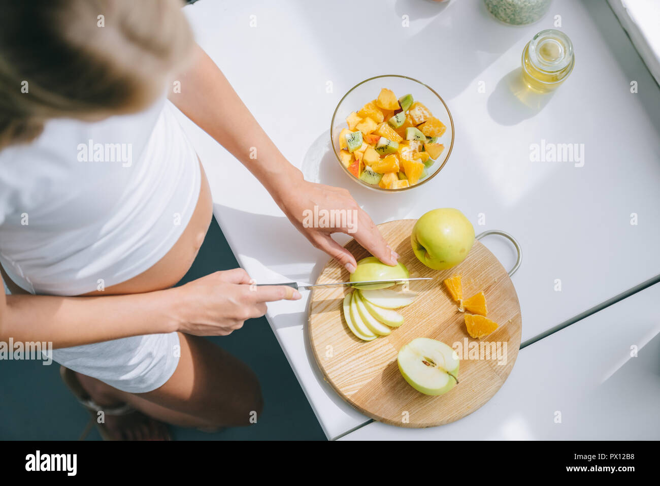 overhead view of pregnant woman with knife cooking fruits salad at home - Stock Image
