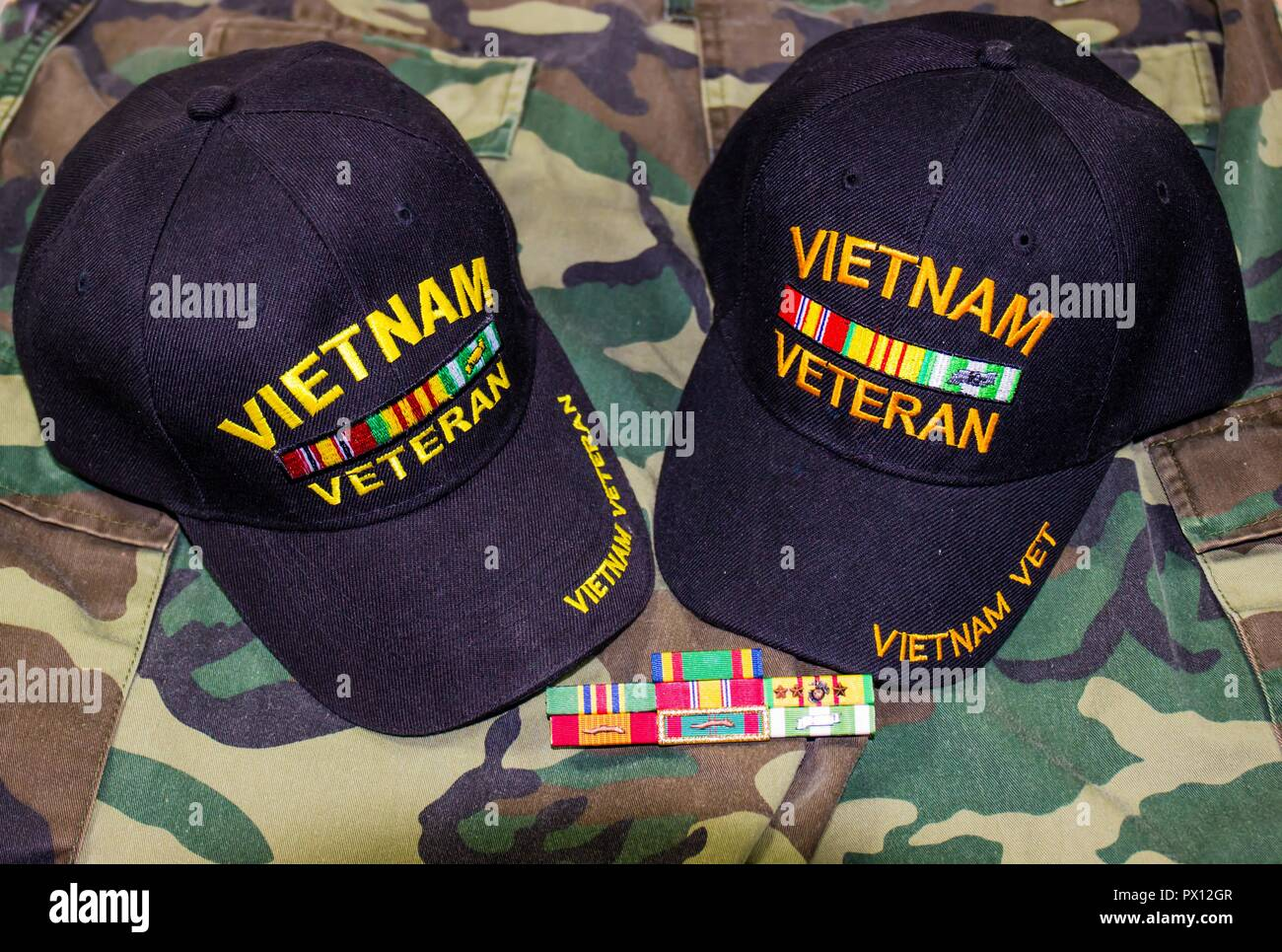 Two Vietnam Veteran Hats With Service Ribbons On Camouflage Uniform - Stock Image