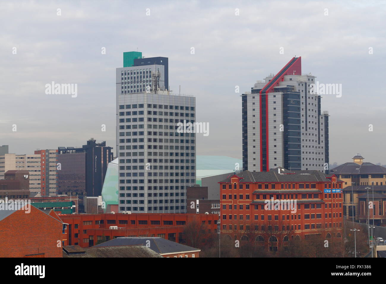 Tall buildings in Leeds towering above the First Direct Arena. - Stock Image