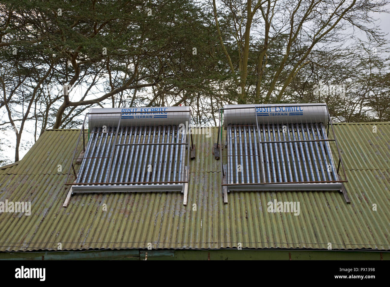 Solar thermal hot water system with storage tank on roof of guest cottage Elsamere Kenya - Stock Image