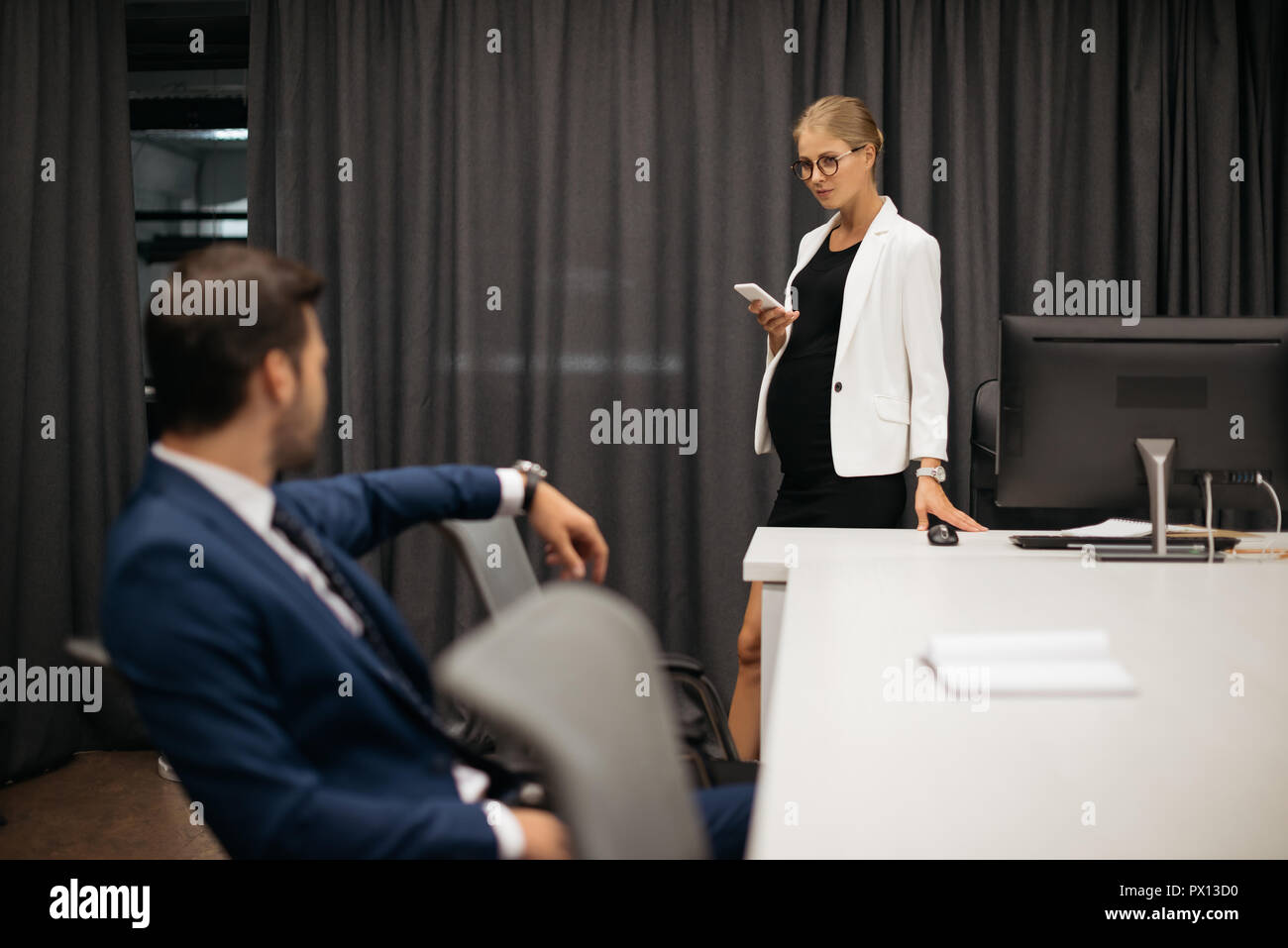 selective focus of businesswoman with smartphone and colleague at workplace in office Stock Photo