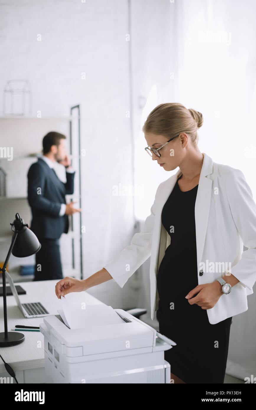 selective focus of pregnant businesswoman using printer while colleague talking on smartphone in office Stock Photo