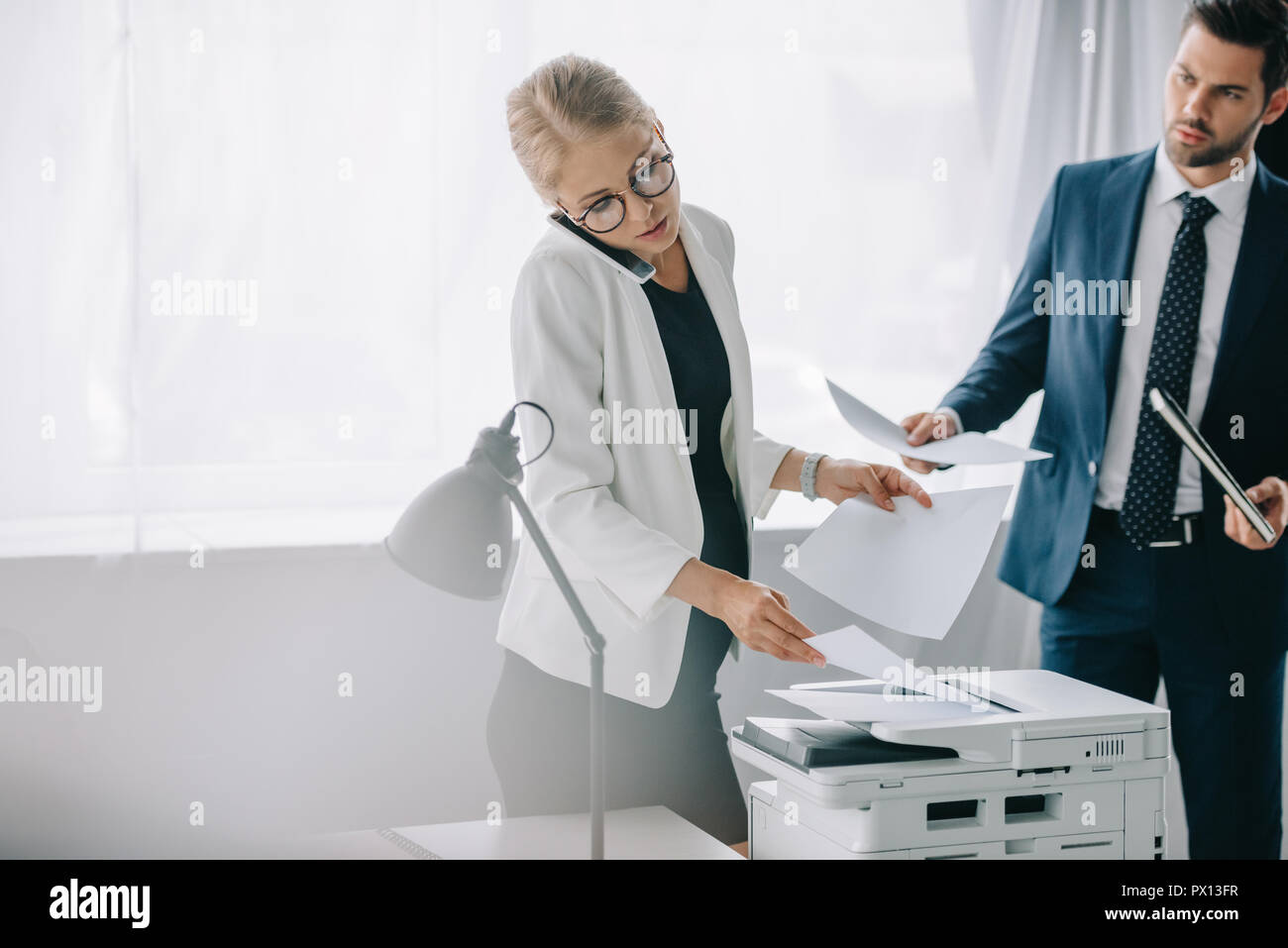 pregnant businesswoman talking on smartphone while using printer and businessman with papers standing behind in office Stock Photo