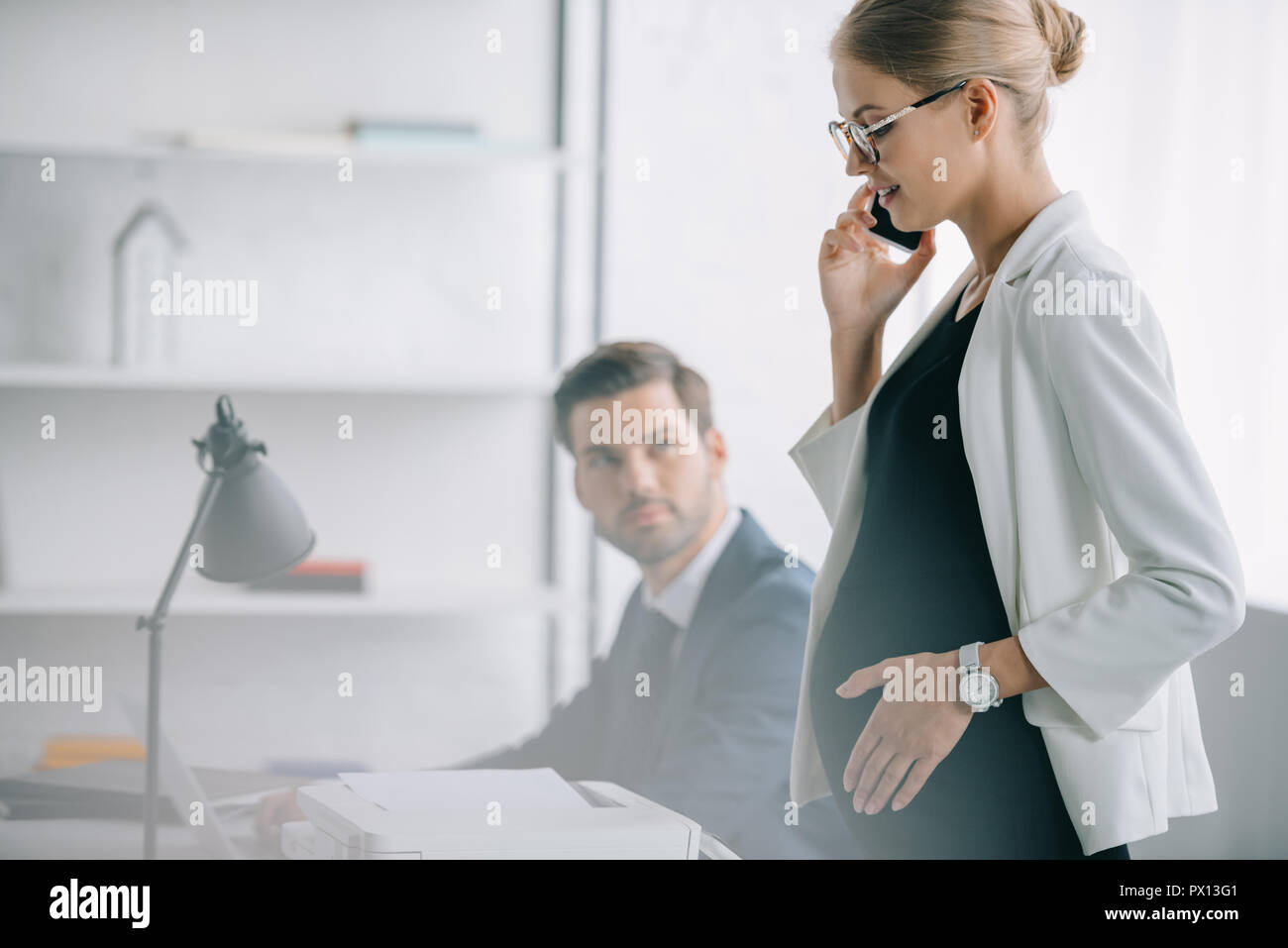smiling pregnant businesswoman talking on smartphone while standing near colleague at workplace in office Stock Photo