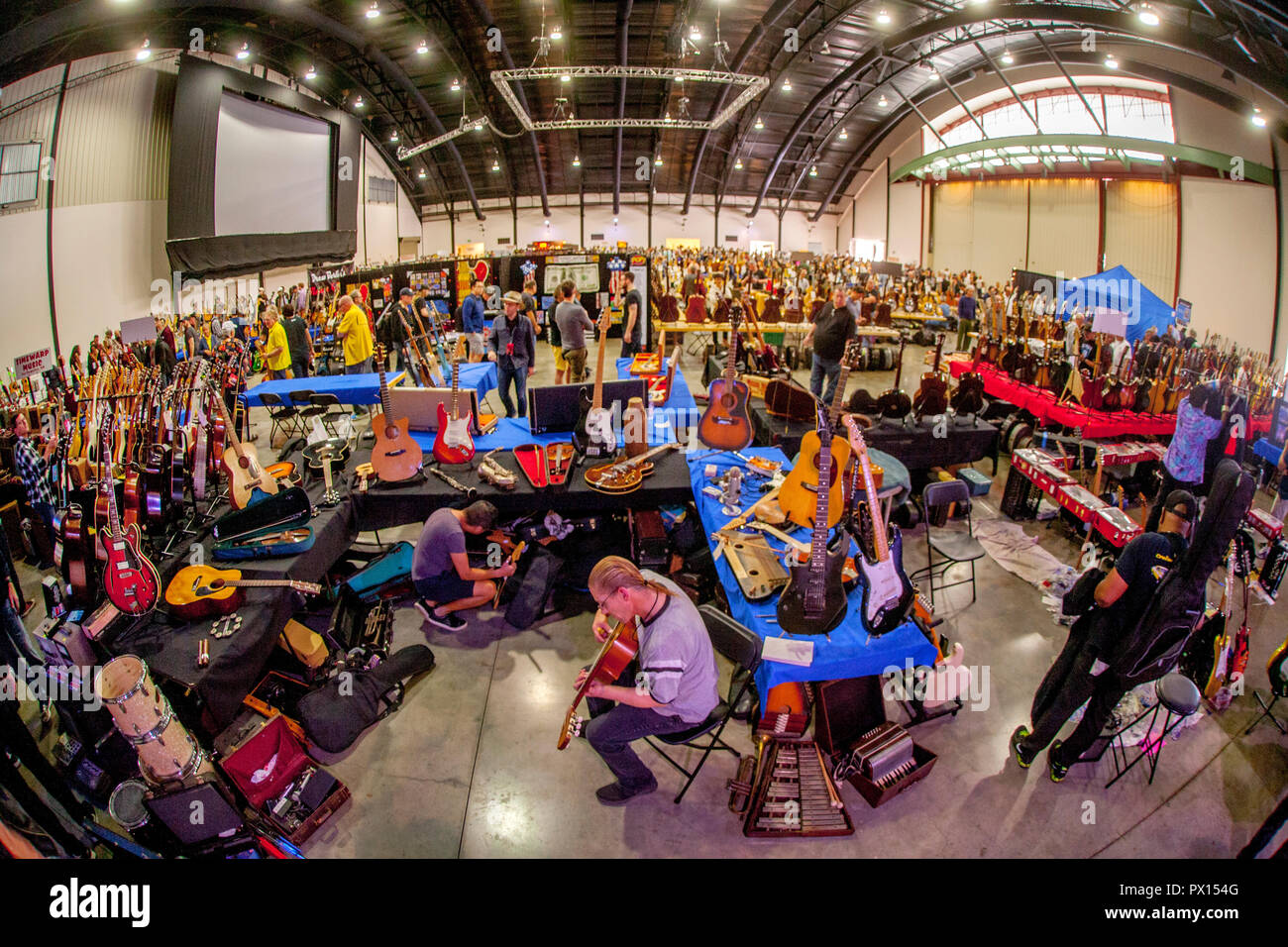 Hundreds of musicians gather at a guitar convention at a converted hanger in Costa Mesa, CA, to play their music and buy and sell instruments. - Stock Image