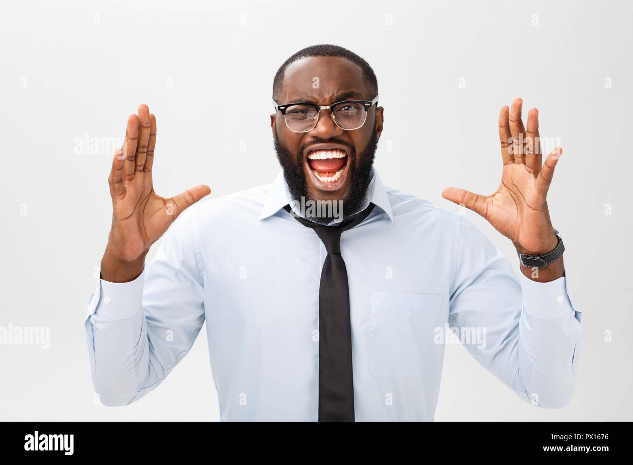 Portrait of desperate annoyed black male screaming in rage and anger tearing his hair out while feeling furious and mad with something. Negative human face expressions, emotions and feelings. Stock Photo