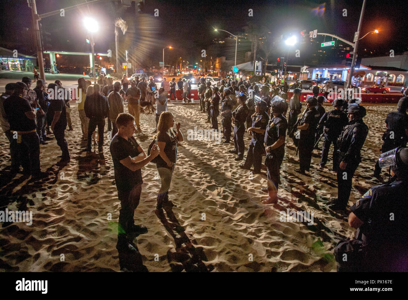 Laguna Beach, CA, police in hard hats line up to separate multiracial demonstrators from counter-demonstrators at a right-wing rally on the city's Main Beach. - Stock Image
