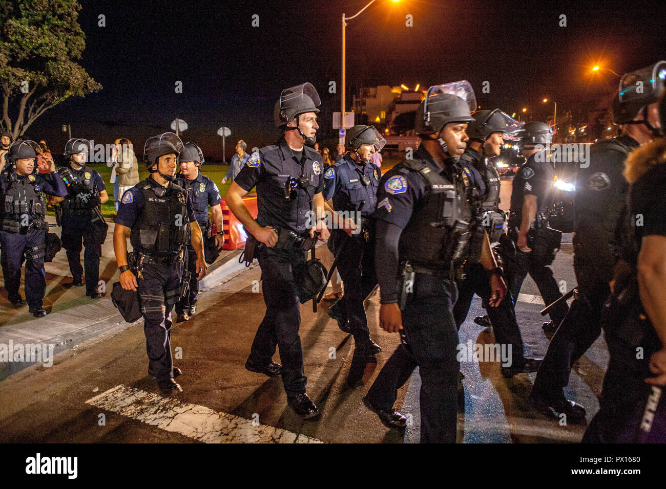 Laguna Beach police in hard hats arrive at a right-wing demonstration at the city's Main Beach. - Stock Image