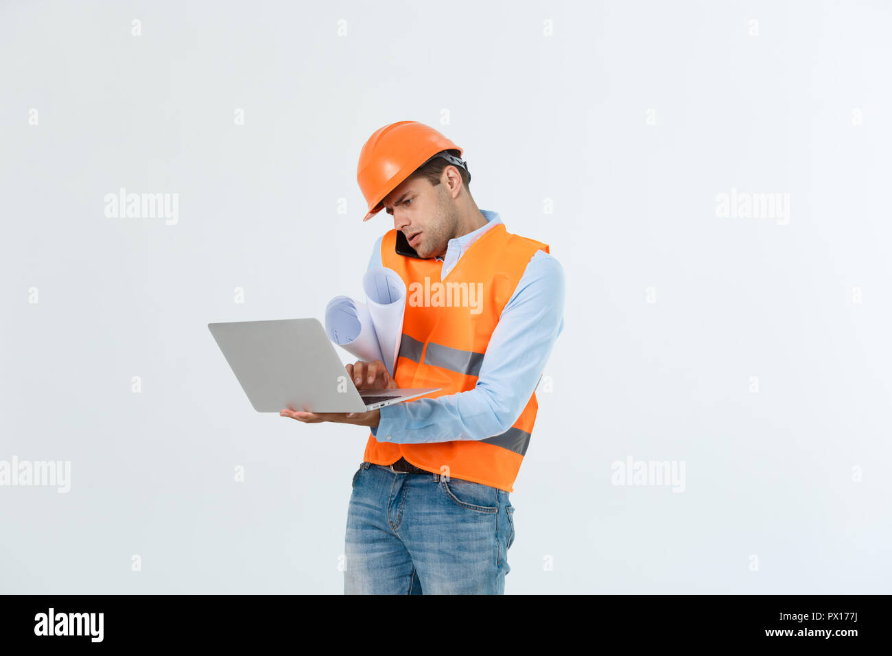 Engineer, architect, on busy face speaks on smartphone while holds blueprints. Man, foreman in helmet speaking on phone, red background. Architect calling engineer to fix plan. Communication concept - Stock Image