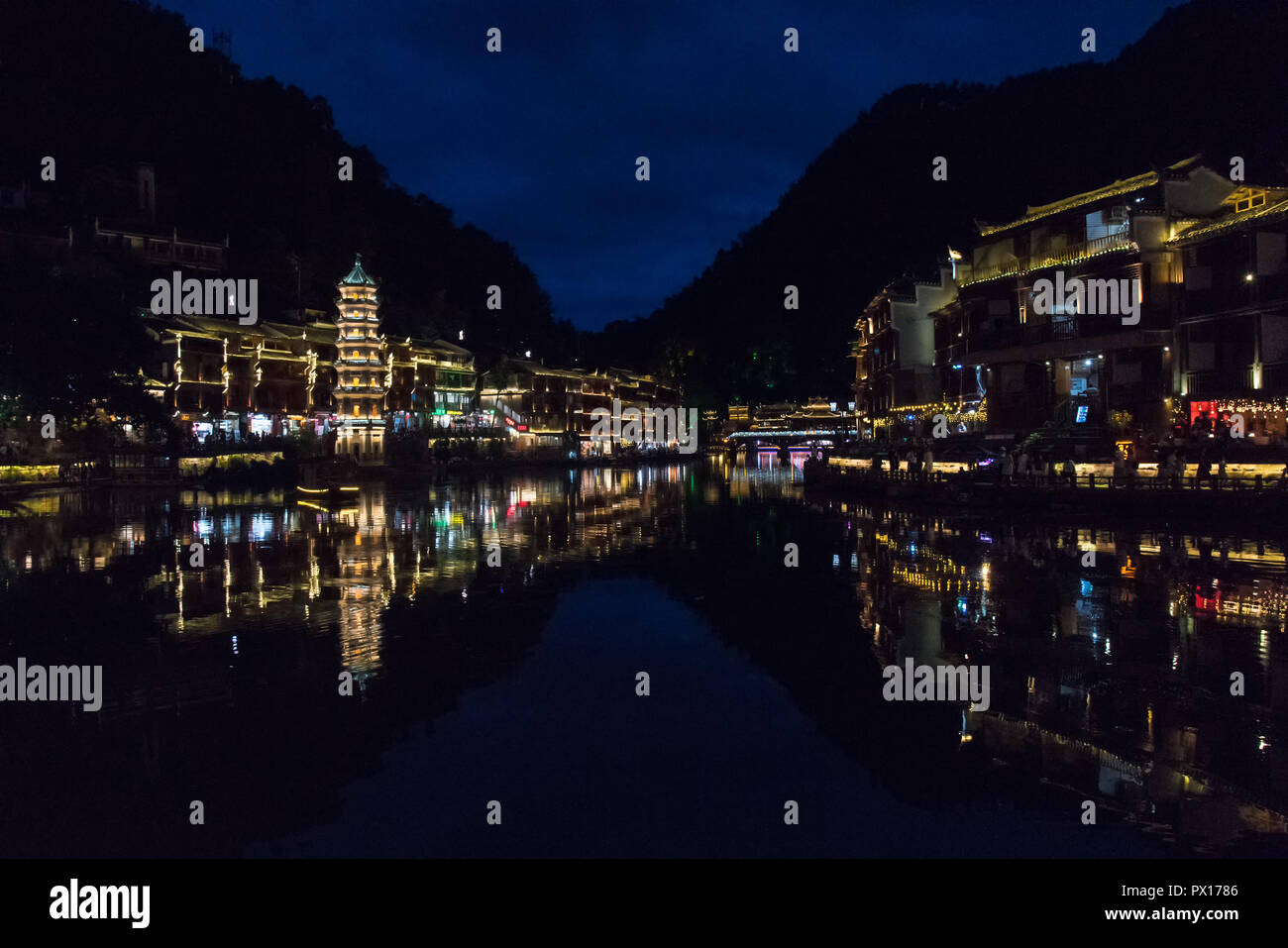FENGHUANG, HUNAN, CHINA - 8JUL2018:  Night-time view of the Tuojiang River and the Wanming Pagoda. - Stock Image
