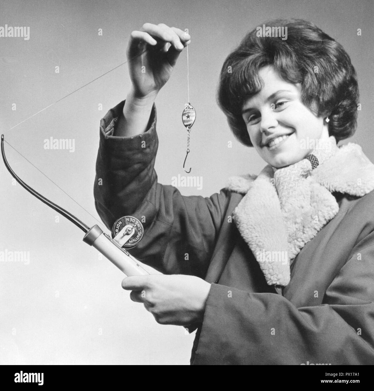 Fishing in the 1960s. A woman is holding an fishing rod and a fishing lure especially used when ice-fishing through a drilled hole in the ice. Sweden 1960s. - Stock Image