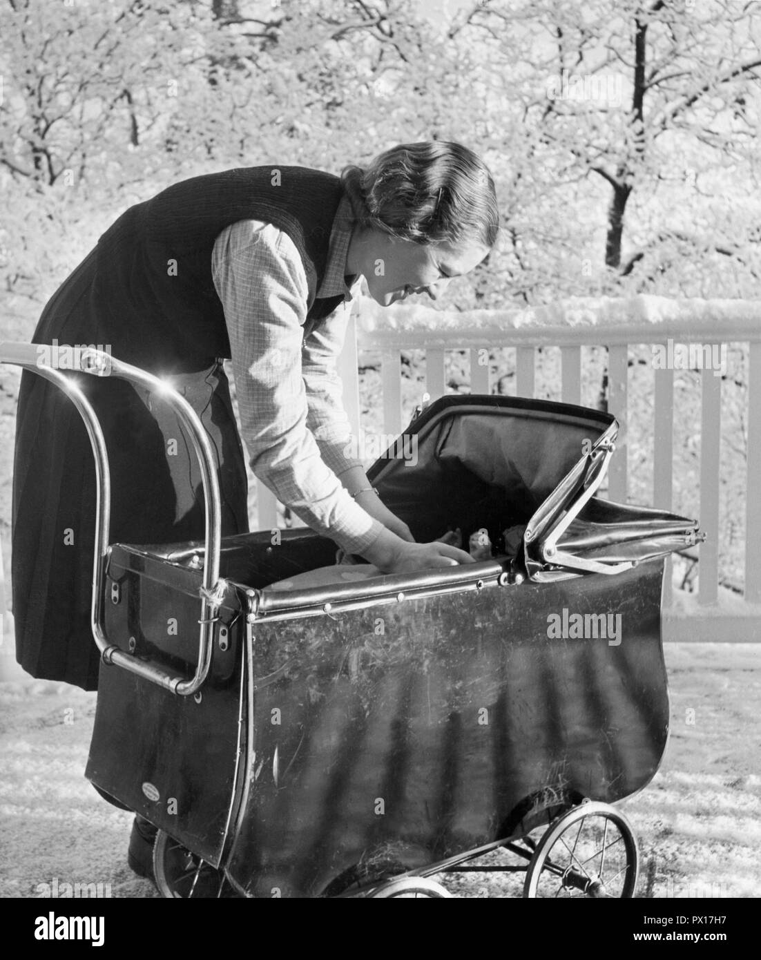 Mother with child in the 1940s. Mrs. Norrby with her daughter Margareta in a stroller on a winters day. Sweden 1942 - Stock Image