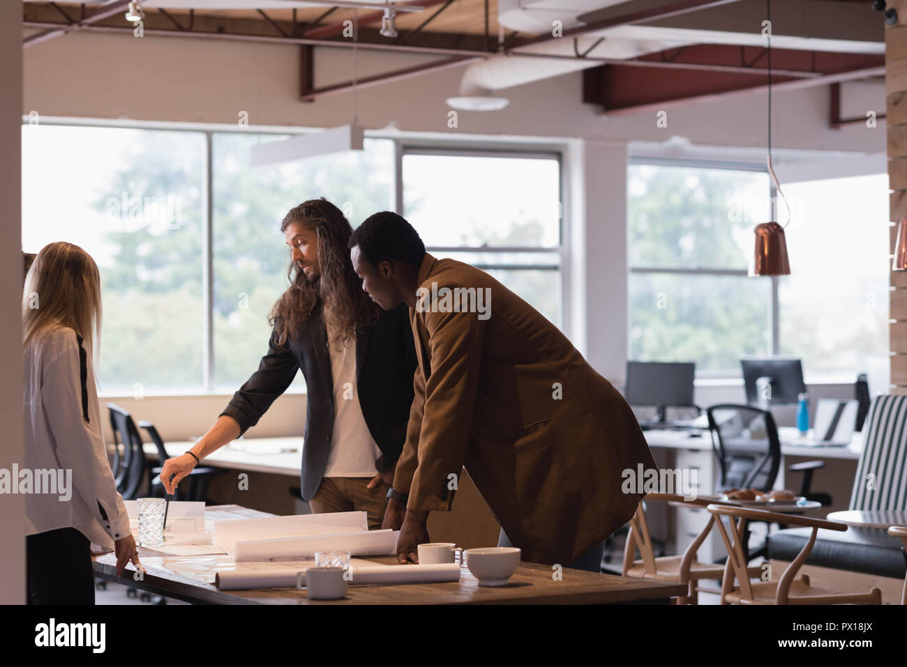 Business people discussing blueprints in the office Stock Photo