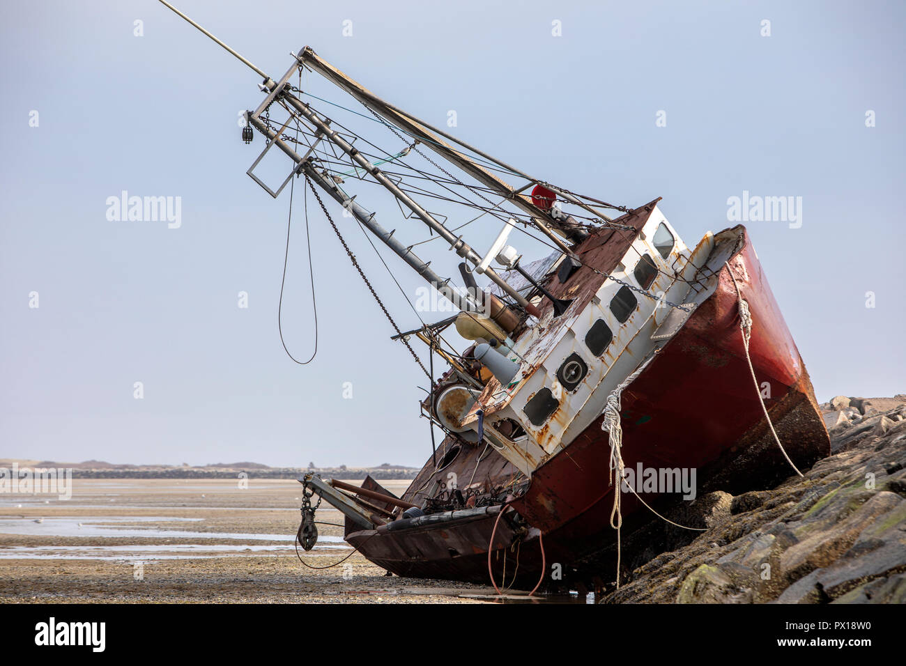 An abandoned derelict fishing boat stranded on a rock jetty. - Stock Image
