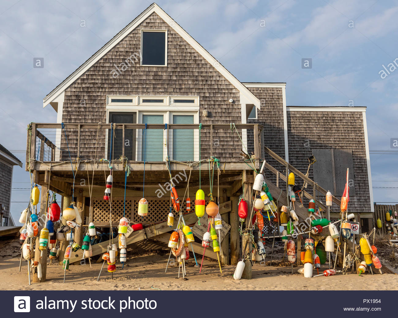 A house with colorful foam fishing buoys decorating the exterior. - Stock Image