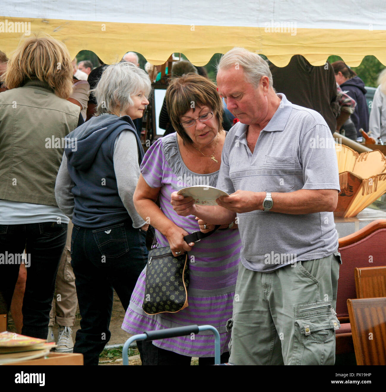 Couples look to a plate of auction gadgets in search of somthing of interest - Stock Image