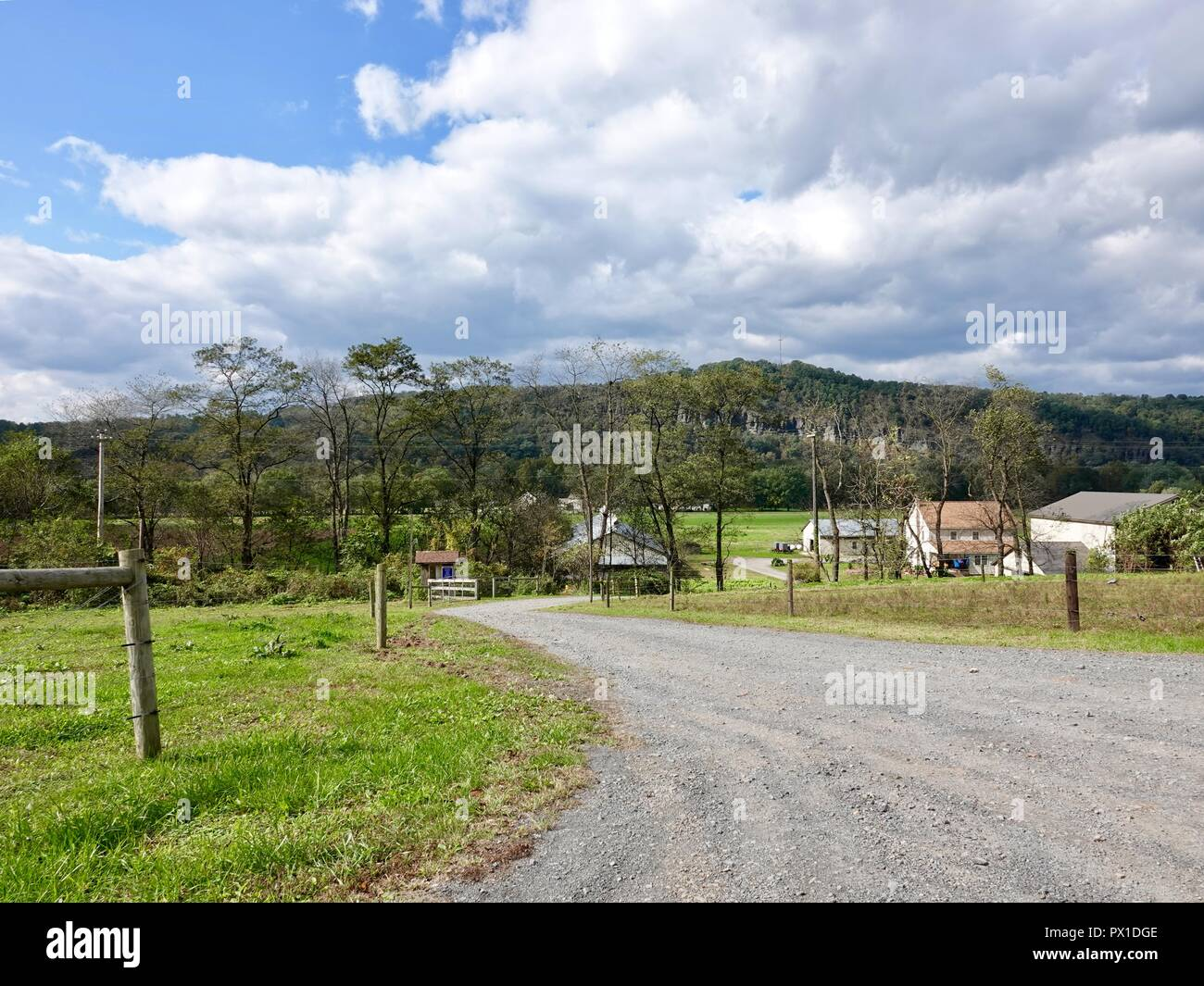 Looking down graded road towards farm land and homes in sparsely populated area of rural Lycoming County, Pennsylvania, USA. - Stock Image