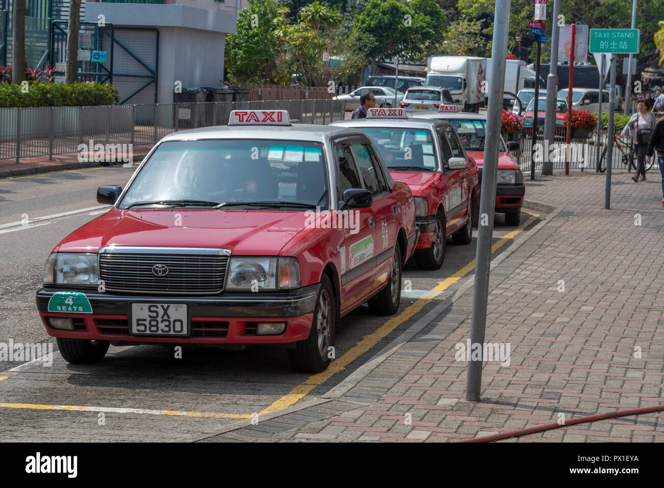 Red Hong Kong taxis in Central District of Hong Kong parked at a local Taxi Stand. - Stock Image