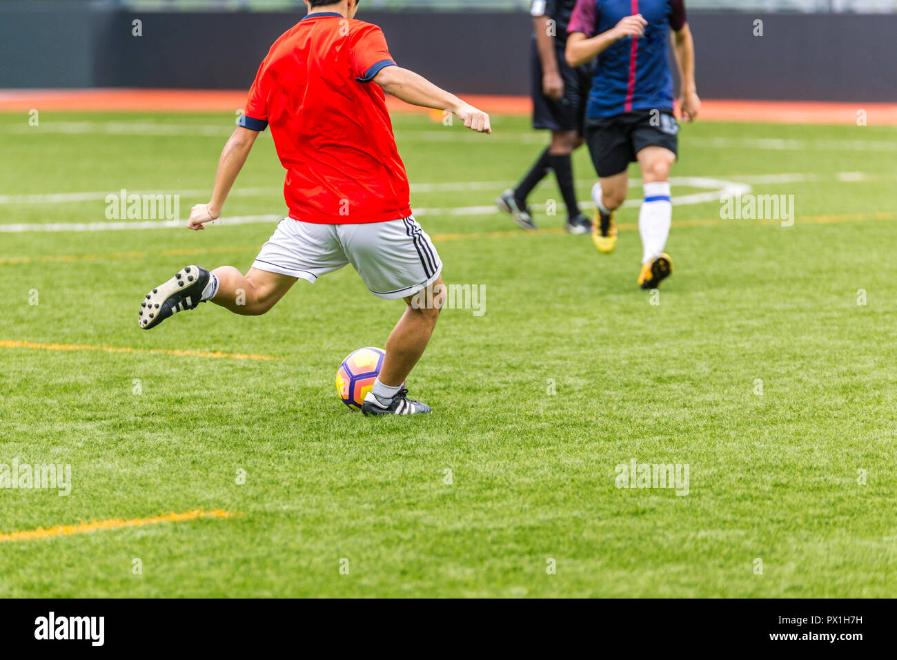 Playing Soccer Football Players in the Stadium Field during Match Competition showing Soccer Ball for Background - Stock Image