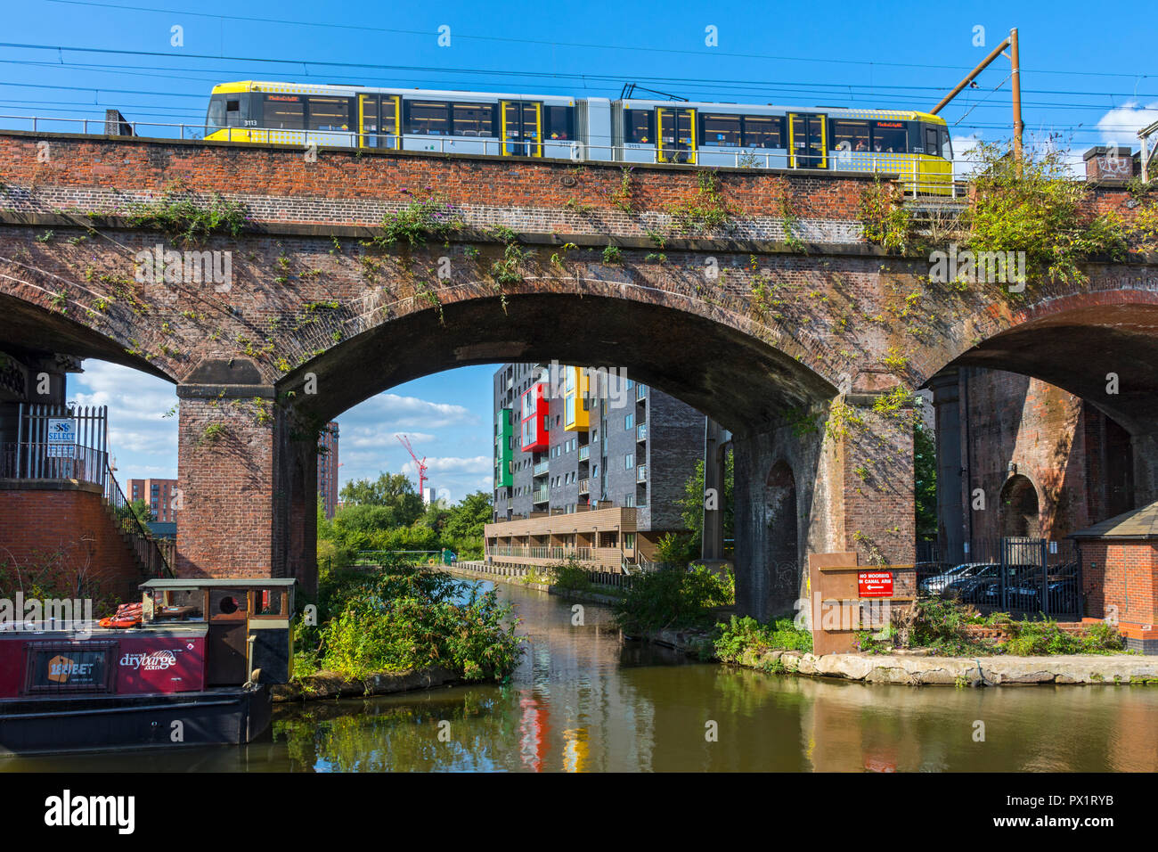 Metrolink tram on a Victorian railway bridge at Potato Wharf on the Bridgewater Canal at Castlefield, Manchester, England, UK Stock Photo