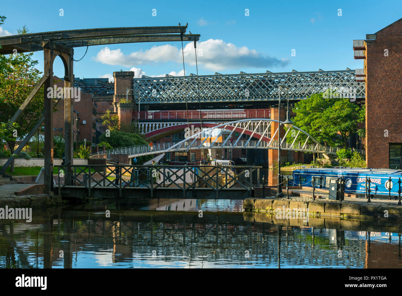 A bascule footbridge, the Merchants' Bridge and Victorian railway viaducts from the Middle Warehouse basin, Castlefield, Manchester, England, UK - Stock Image