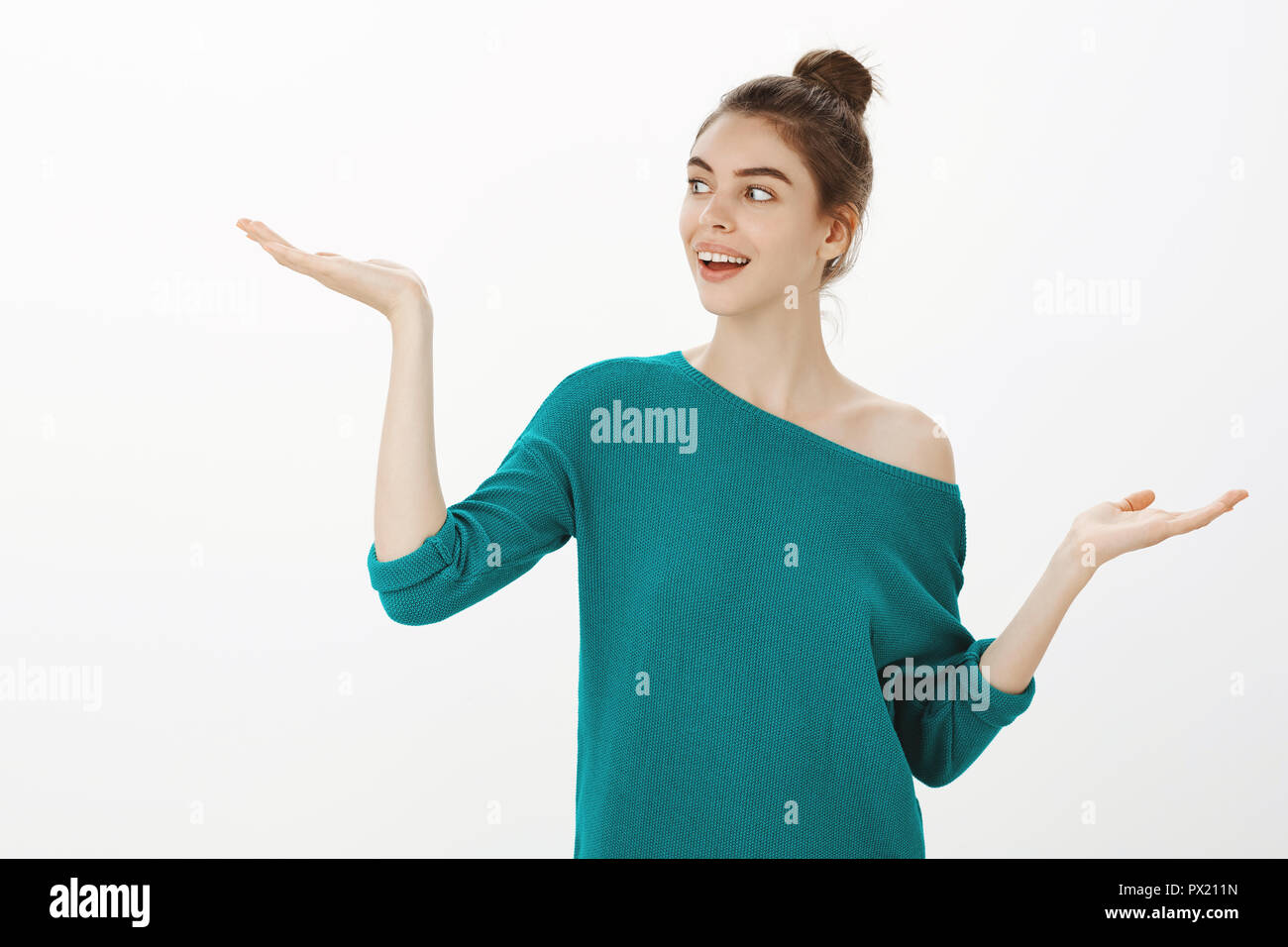 Girl weight choices and made decision. Portrait of good-looking happy woman with bun hairstyle, looking at raised palm while thinking about opportunities, smiling while gazing left over gray wall - Stock Image