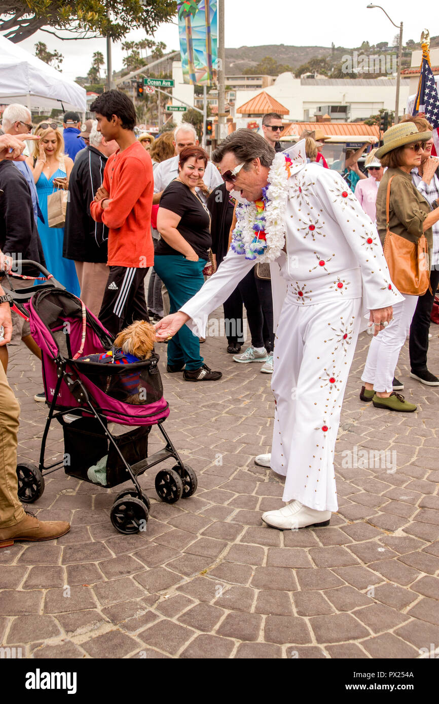 A costumed Elvis Presley impersonator serenades a stroller-riding pooch at an outdoor music festival in Laguna Beach, CA.. - Stock Image
