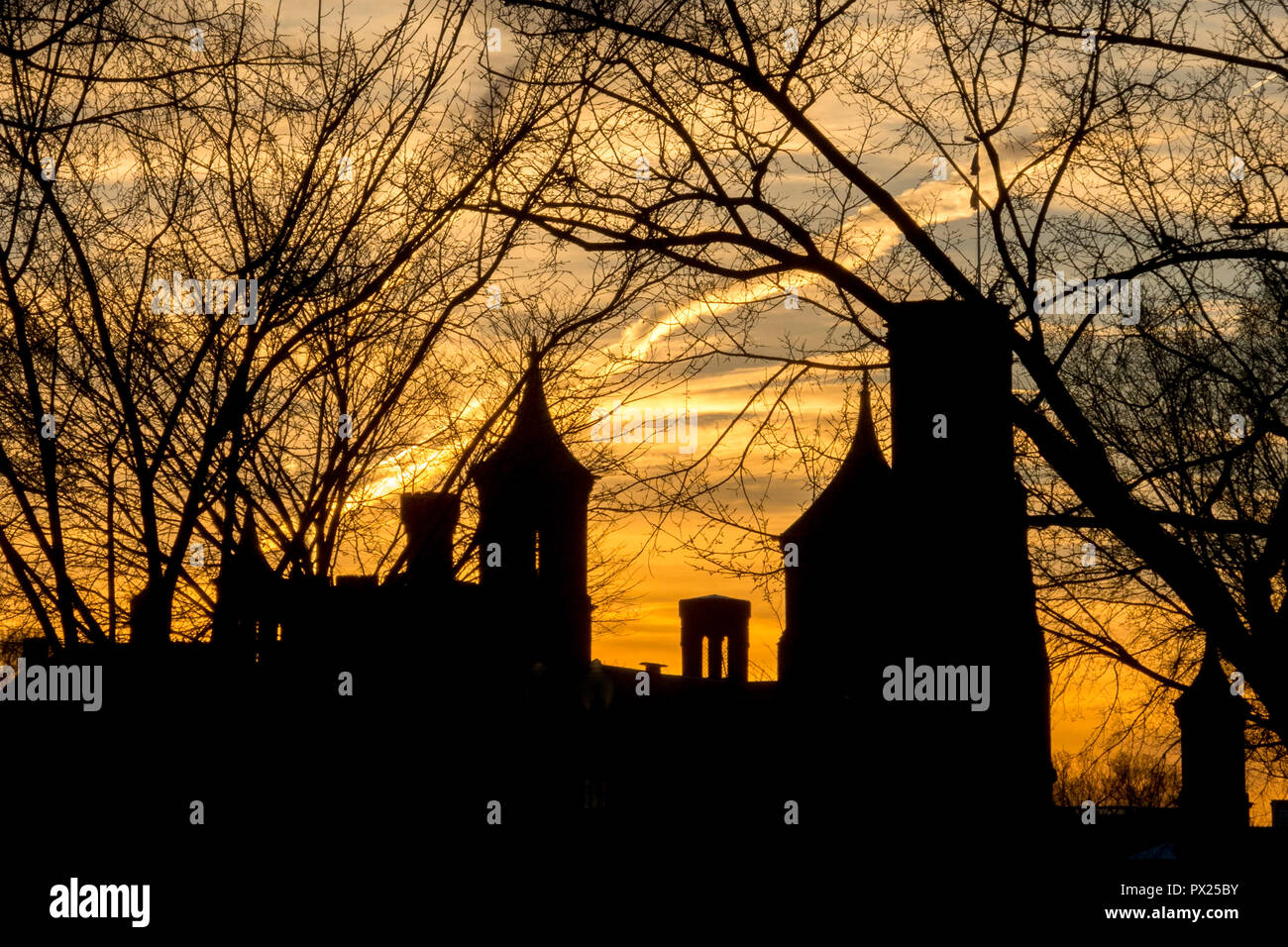 The historic 1855 Smithsonian Institution Administration Building on the National Mall in Washington, DC is silhouetted against a winter sunset and framed by bare tree branches. - Stock Image