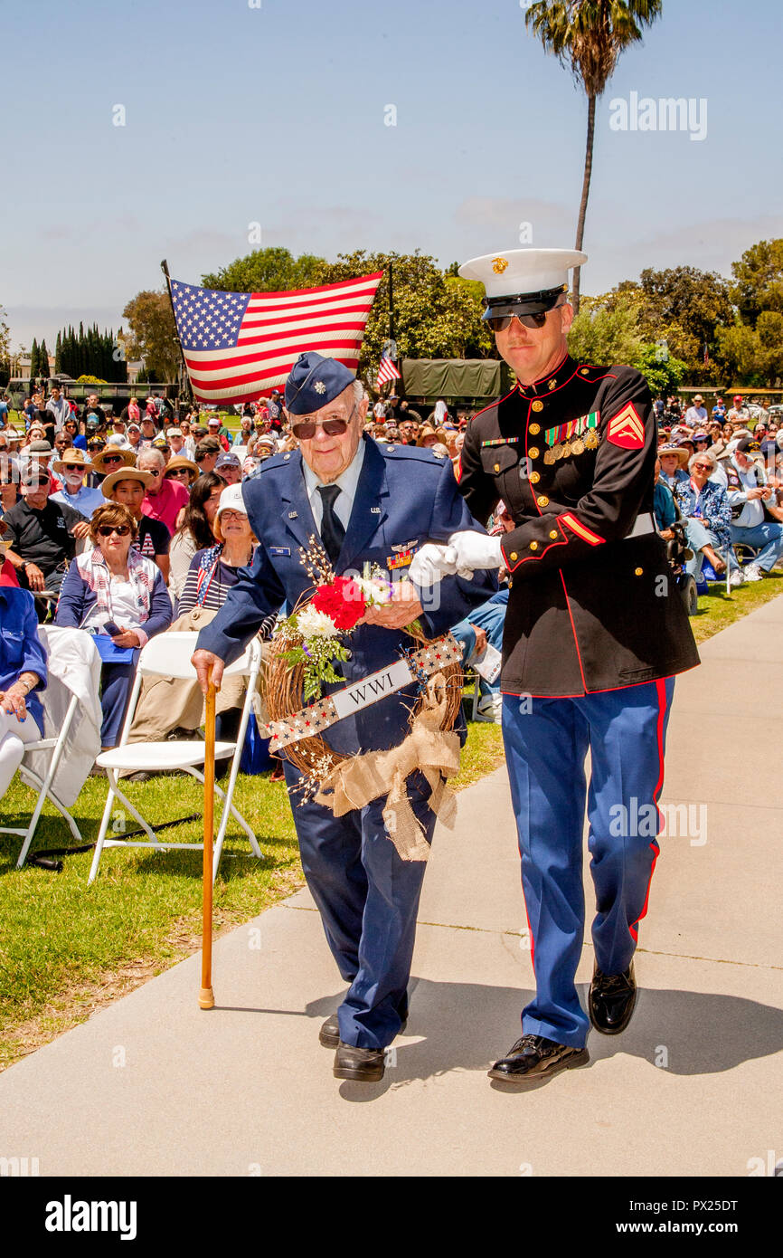 An elderly US Air Force veteran carries a wreath with the assistance of a US Marine corporal during Memorial Day ceremonies at a Costa Mesa, CA,cemetery. - Stock Image