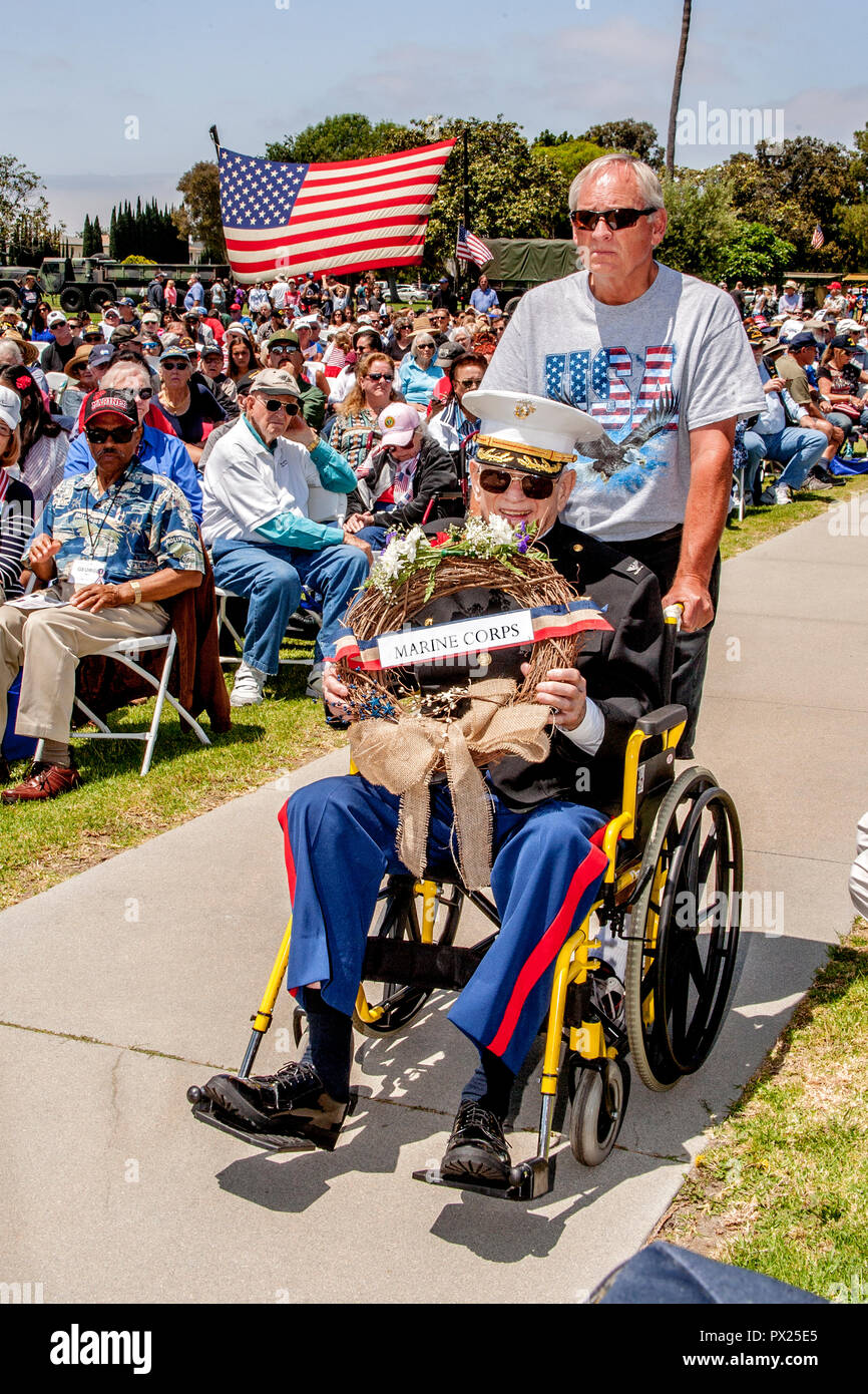 An elderly US Marine veteran in a wheelchair carries a wreath during Memorial Day ceremonies at a Costa Mesa, CA,cemetery. - Stock Image