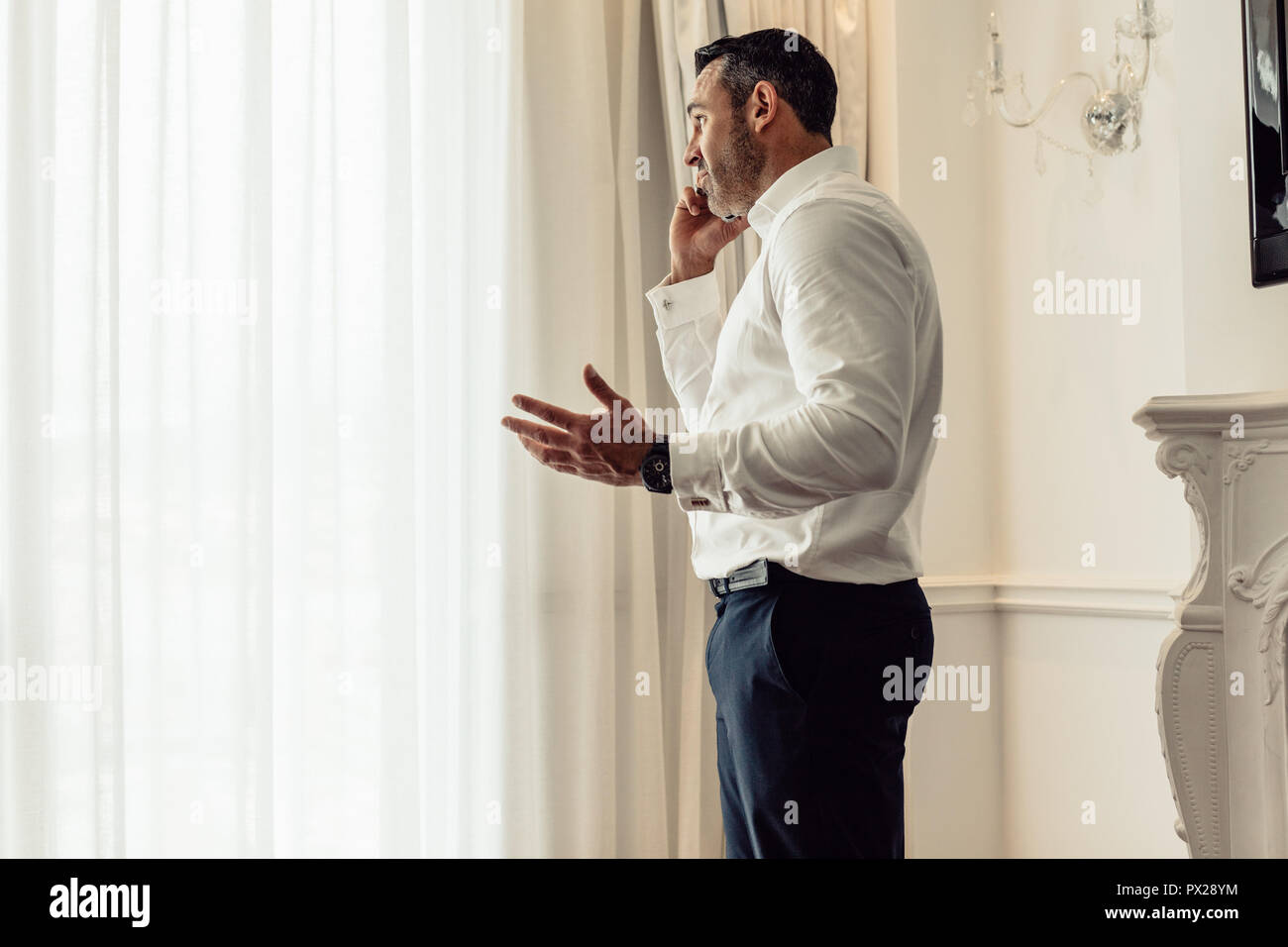 Side view of businessman talking on mobile phone while standing in hotel room. CEO having an important discussing over phone. - Stock Image