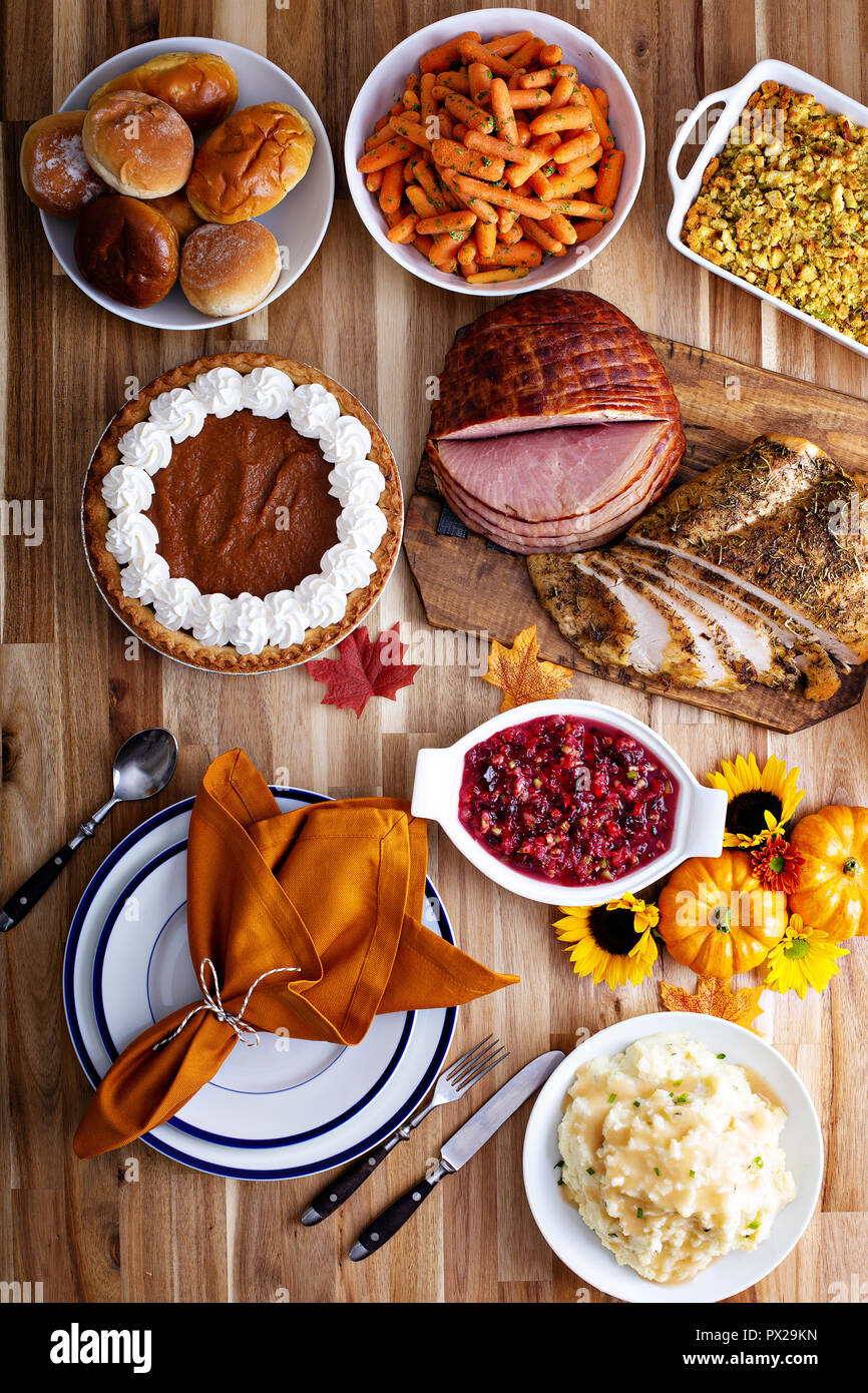 Thanksgiving Table With Roasted Turkey Sliced Ham And Side Dishes Stock Photo Alamy