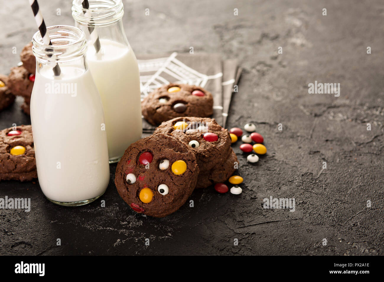 Chocolate cookies with candy and sugar eyeballs with milk for Halloween - Stock Image