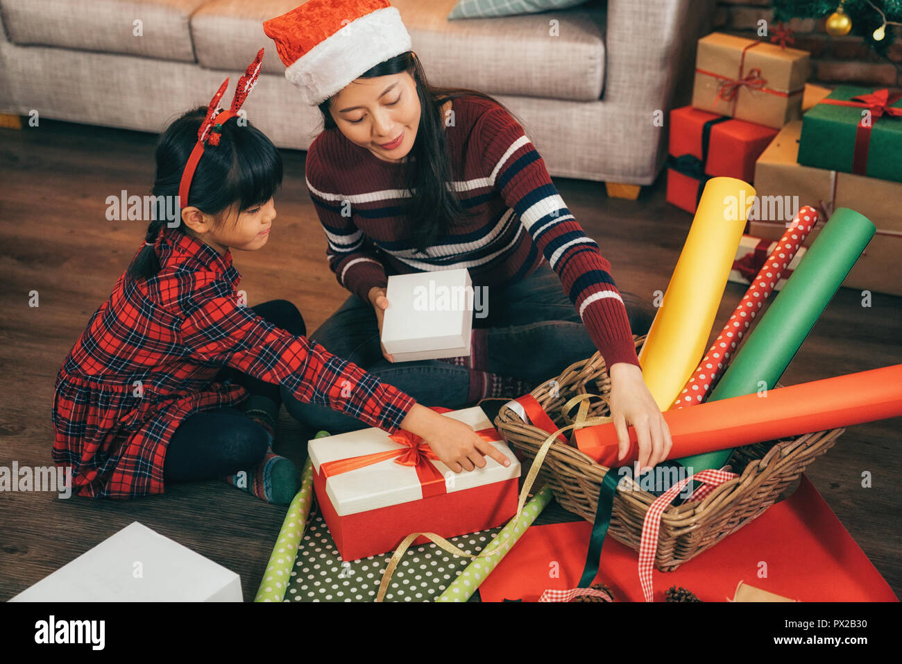 Parent and little child having fun near Christmas gifts indoors ...