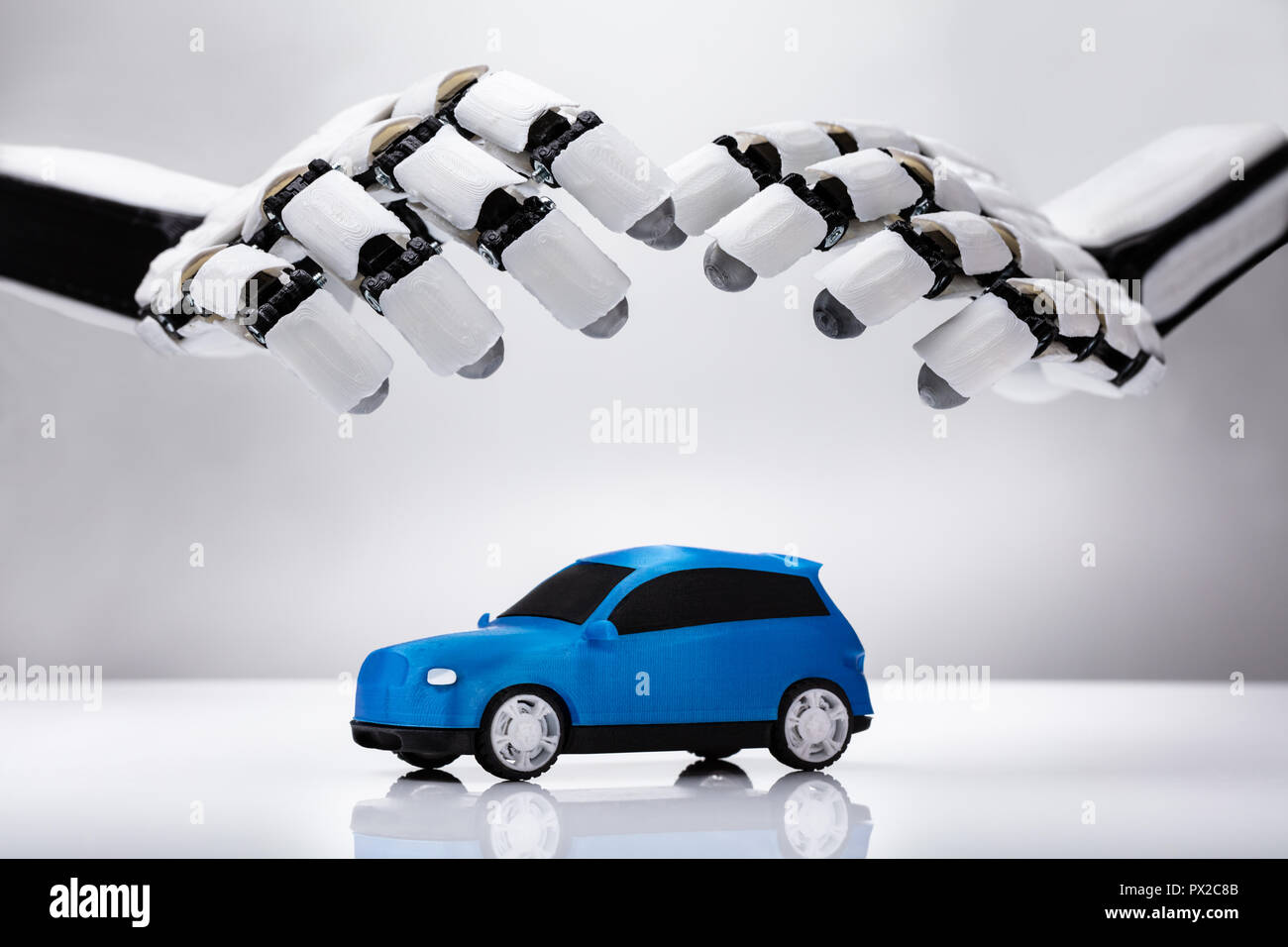 Close-up Of A Robotic Hand Protecting Blue Car On Reflective Desk - Stock Image