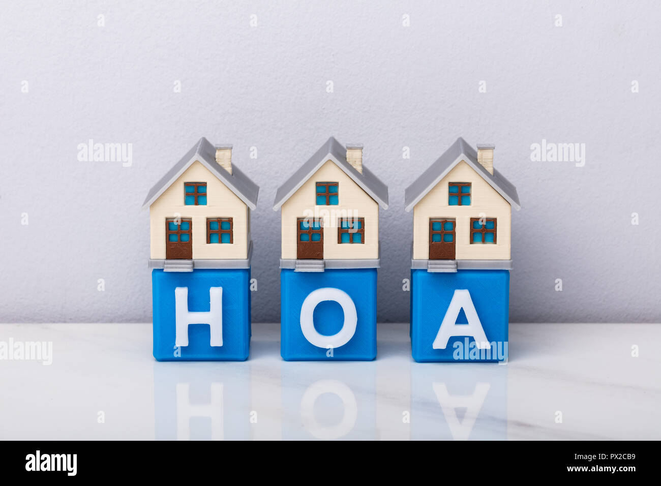 Row Of House Models On Blue HOA Cubic Blocks Over Reflective Desk - Stock Image