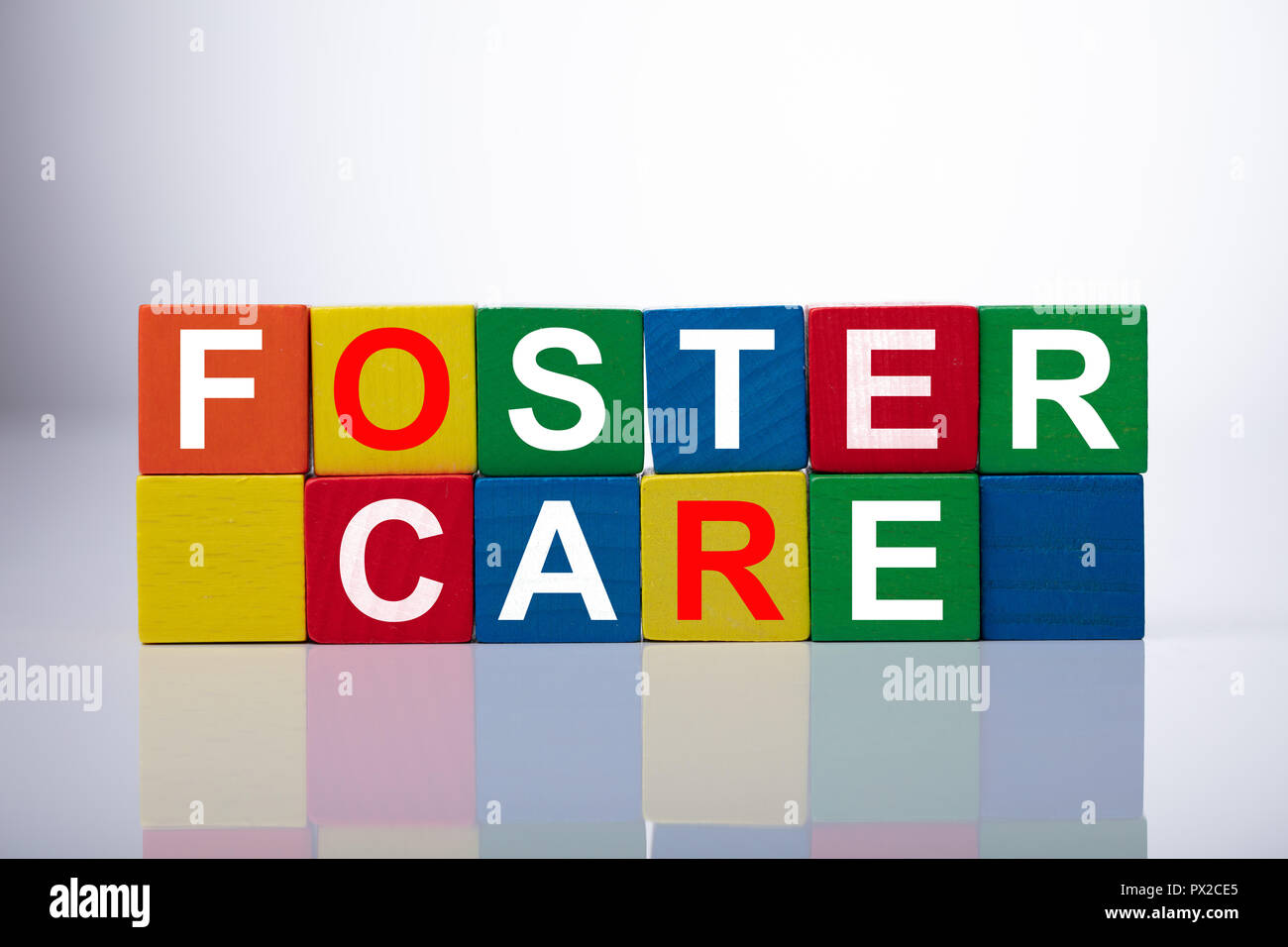 Close-up Of Foster Care Cubic Blocks On Reflective Background - Stock Image