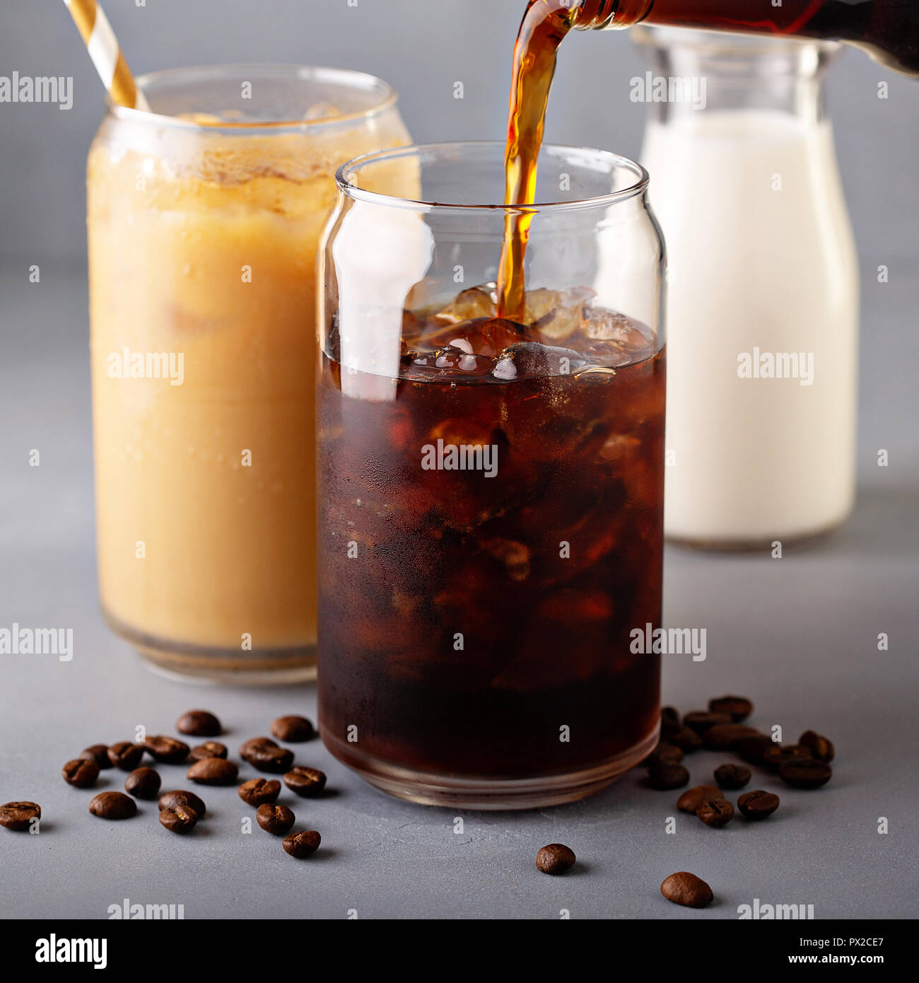 Cold brew iced coffee in glass bottle pouring over - Stock Image