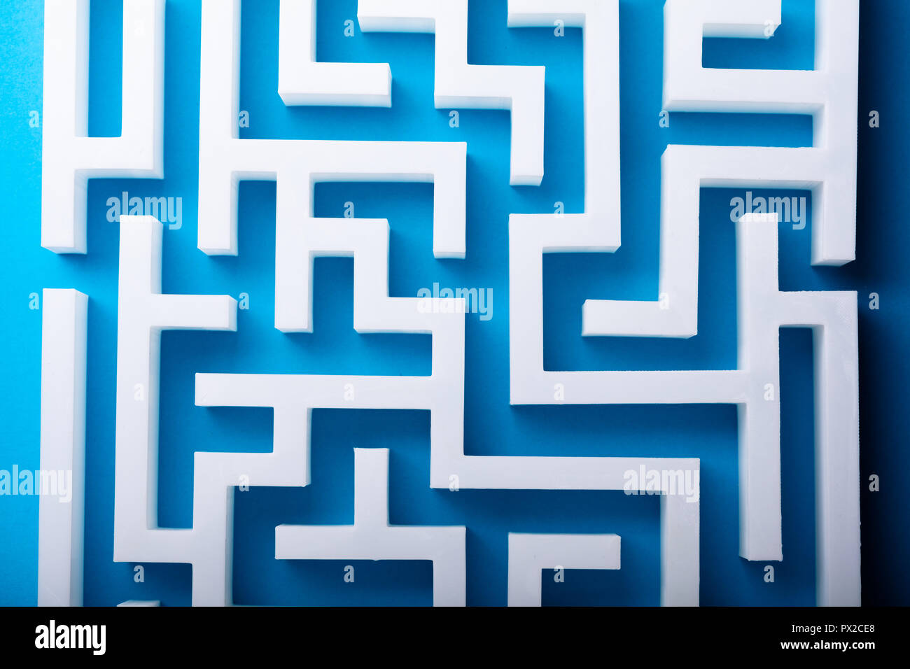 High Angle View Of White Maze On Blue Background - Stock Image