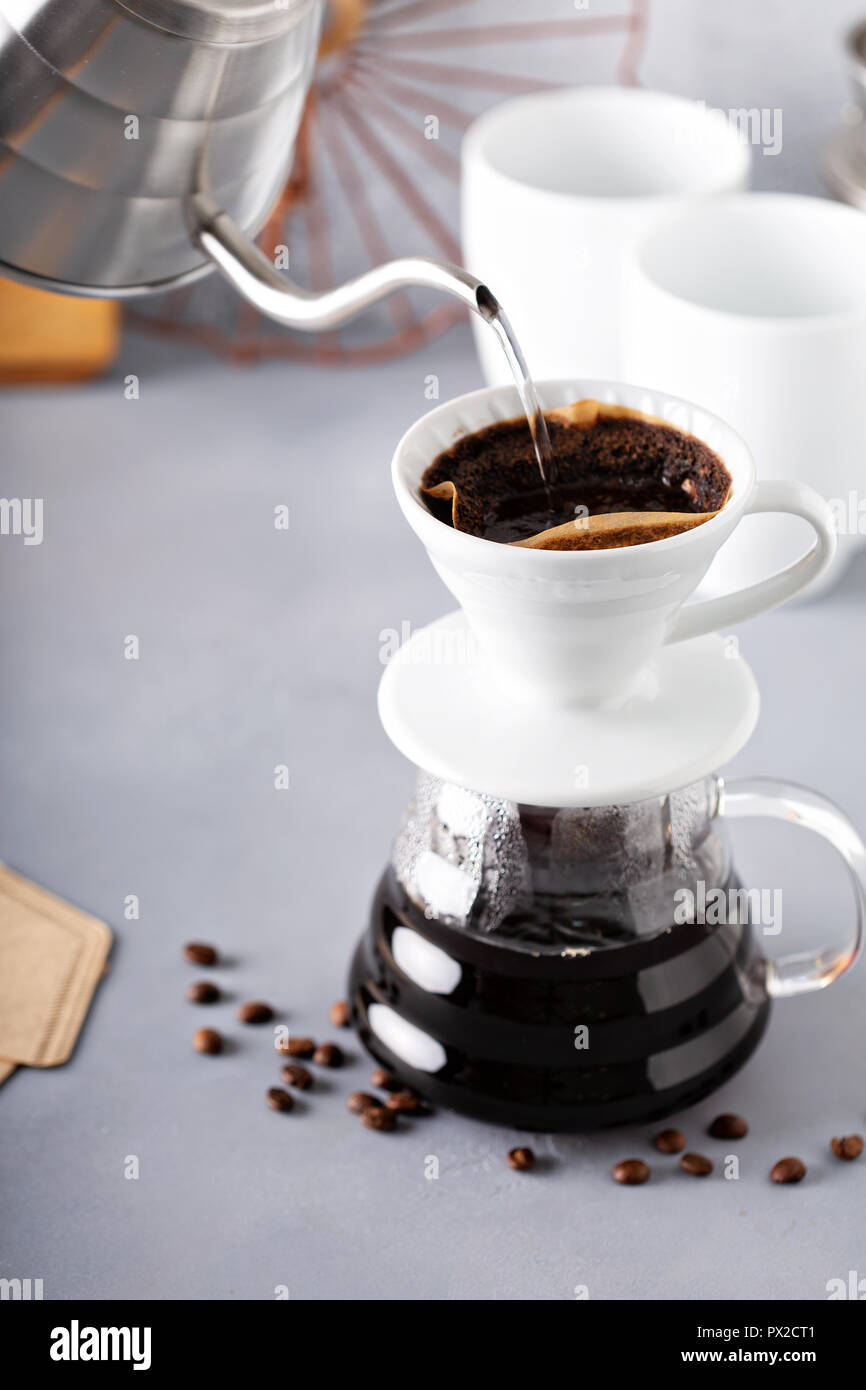 Pour over coffee being made with a kettle and glass carafe with hot water being poured - Stock Image