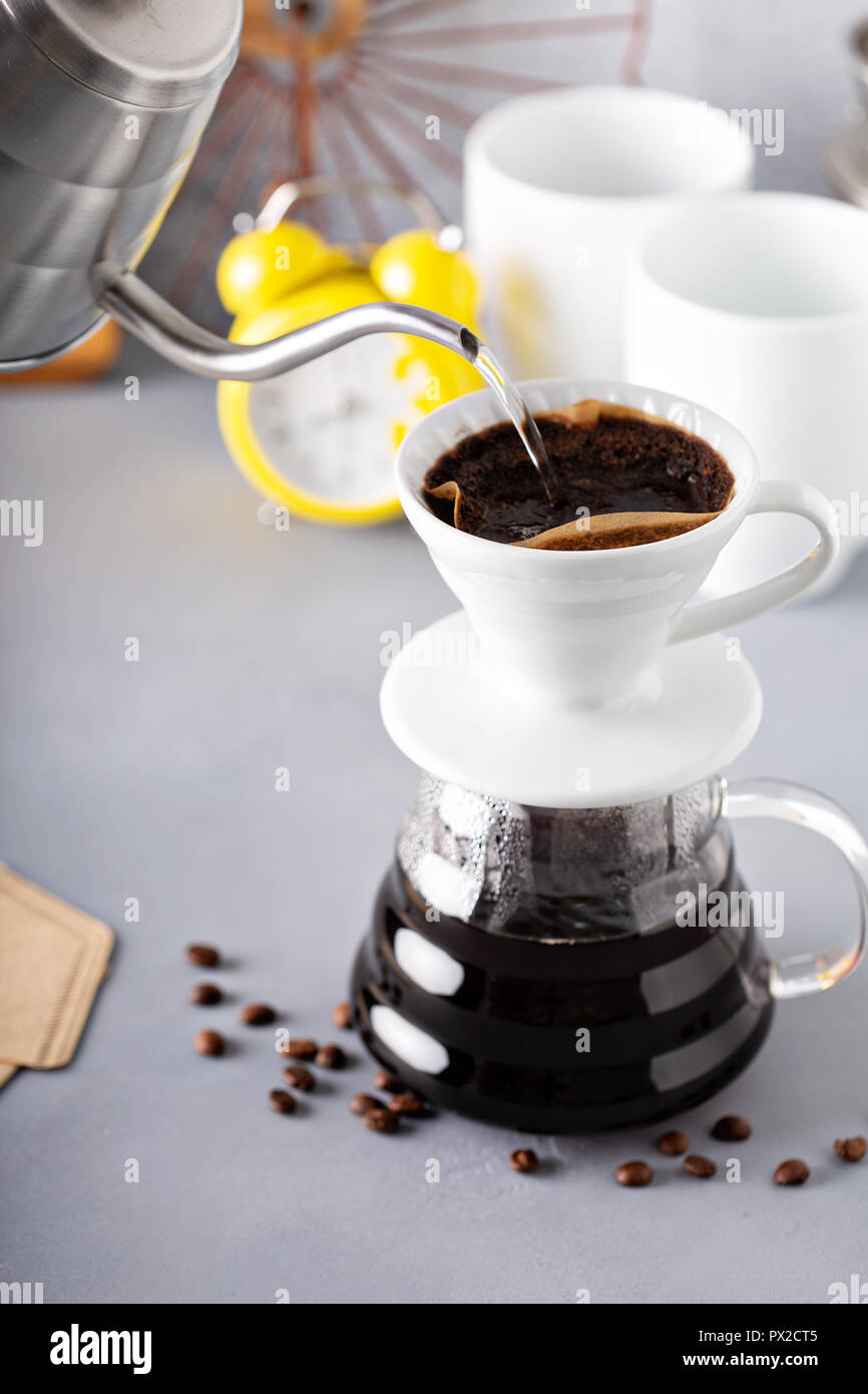 Pour over coffee being made with a kettle and glass carafe with hot water being poured and alarm clock in the background - Stock Image
