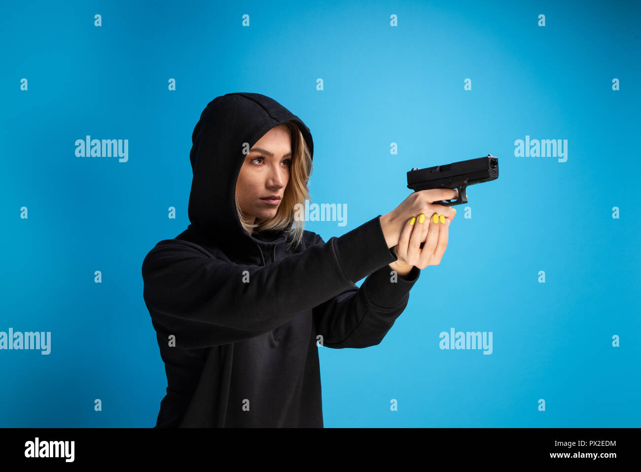 Hooded girl holding a gun pointed to the right side. Criminal face adult gangster - Stock Image