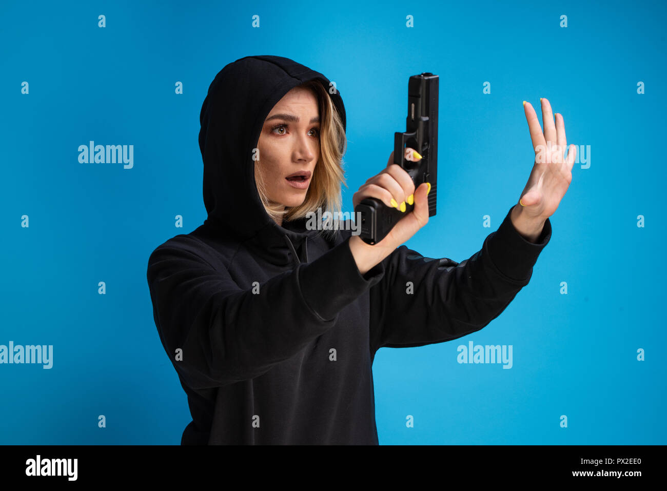 Hooded young girl presenting gun while surrendering. Airsoft game loser - Stock Image