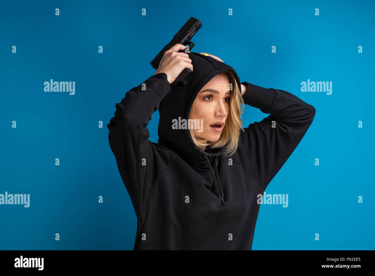 Portrait of hooded girl looking shocked while holding her hands with gun up on the head. Shot against blue background - Stock Image