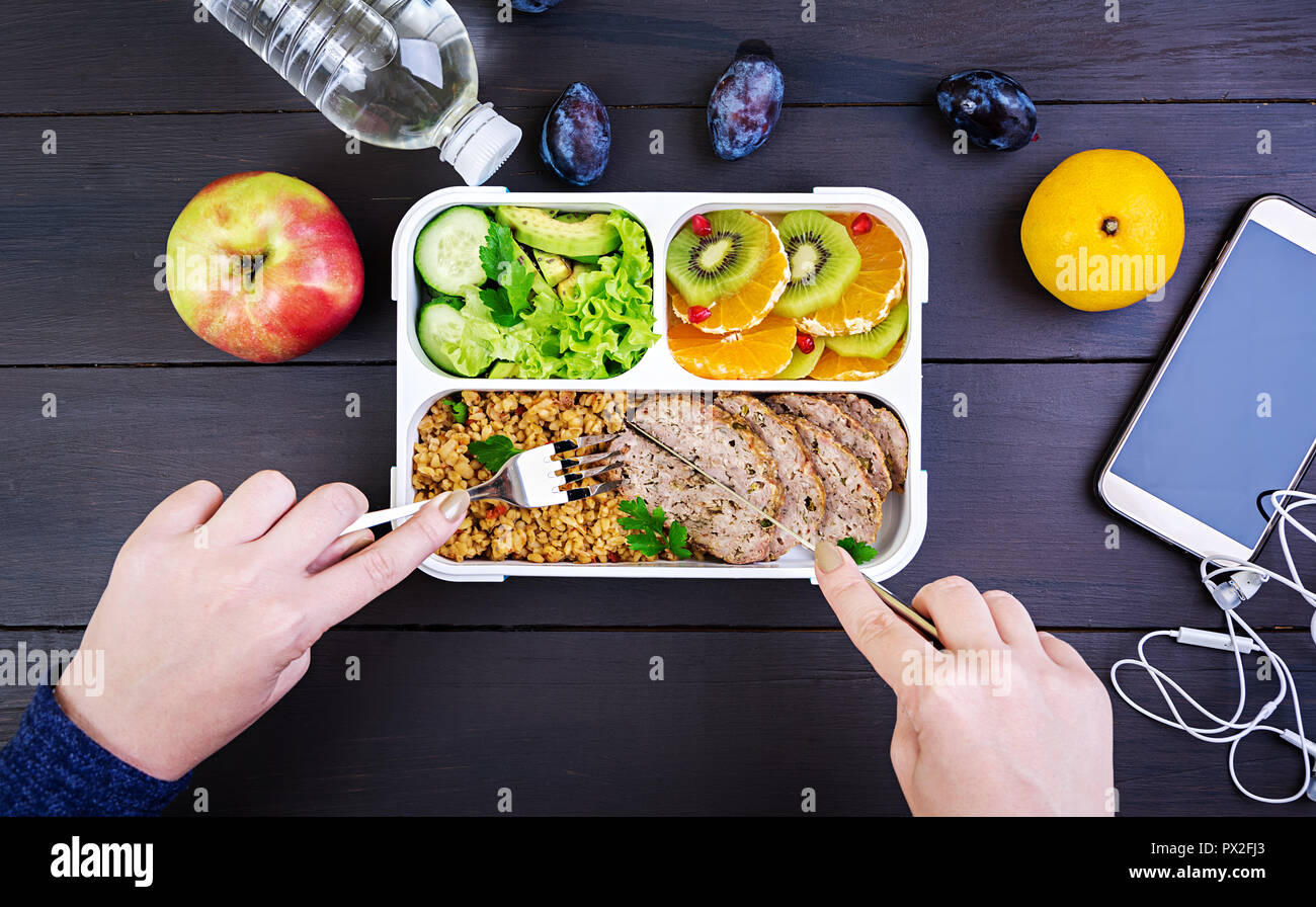Top view showing hands eating healthy lunch with bulgur, meat and fresh vegetables and fruit on a wooden table. Fitness and healthy lifestyle concept. - Stock Image