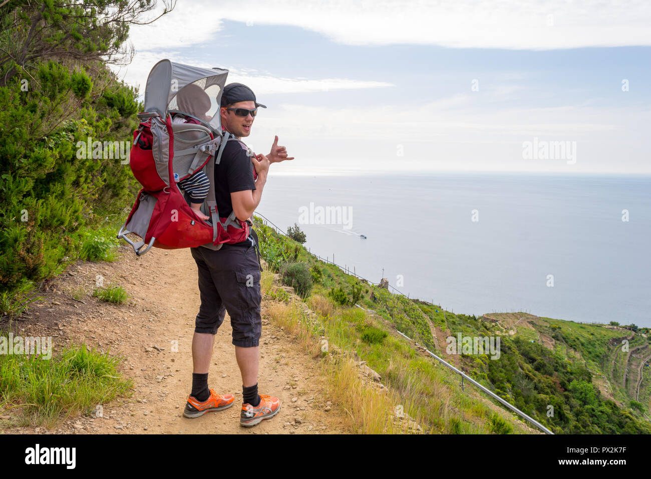 Active Father Carrying A Baby Carrier And Walking Along A Coastal