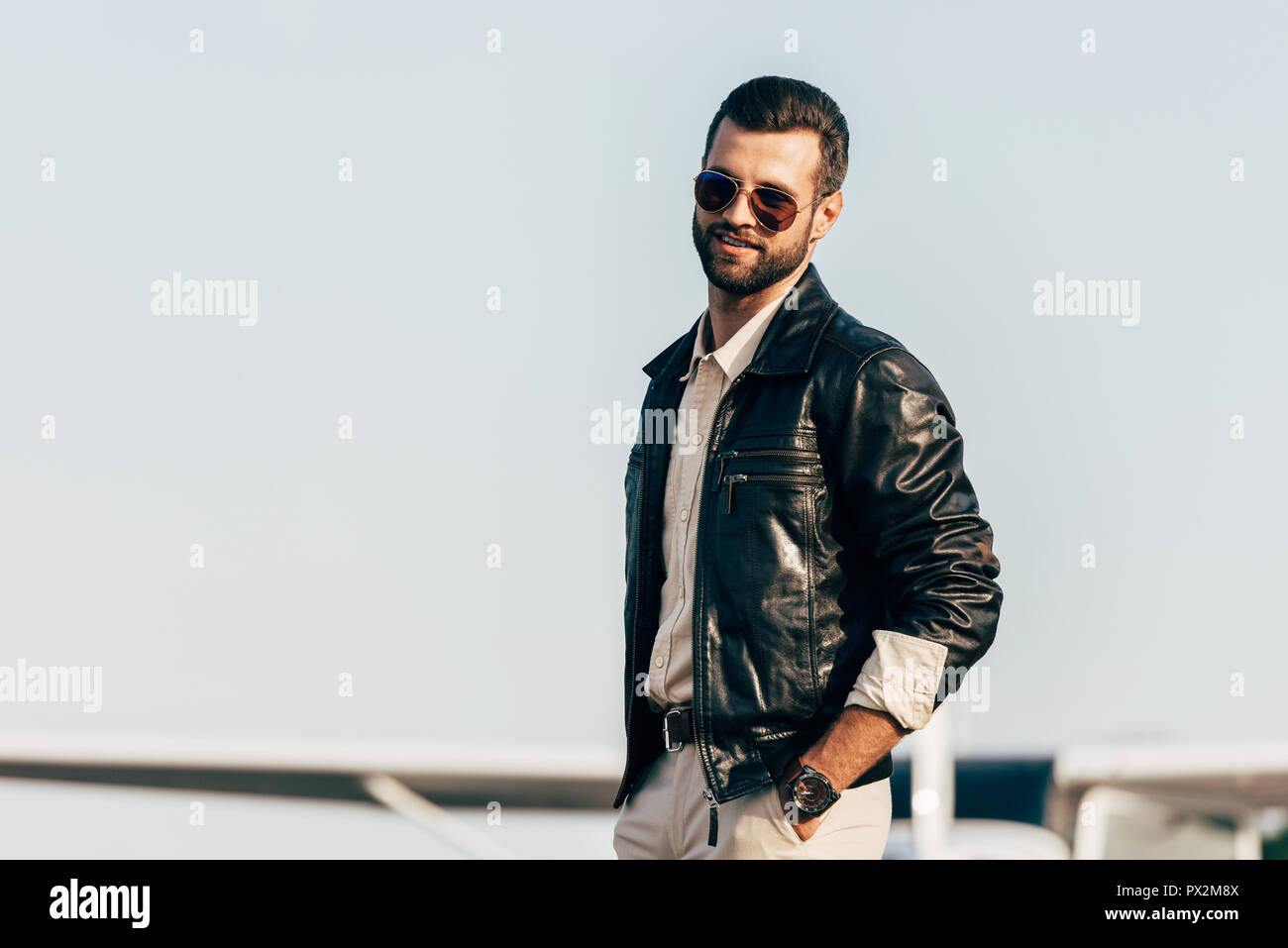 b579f4ebb30 young handsome male pilot in leather jacket and sunglasses posing near  airplane - Stock Image