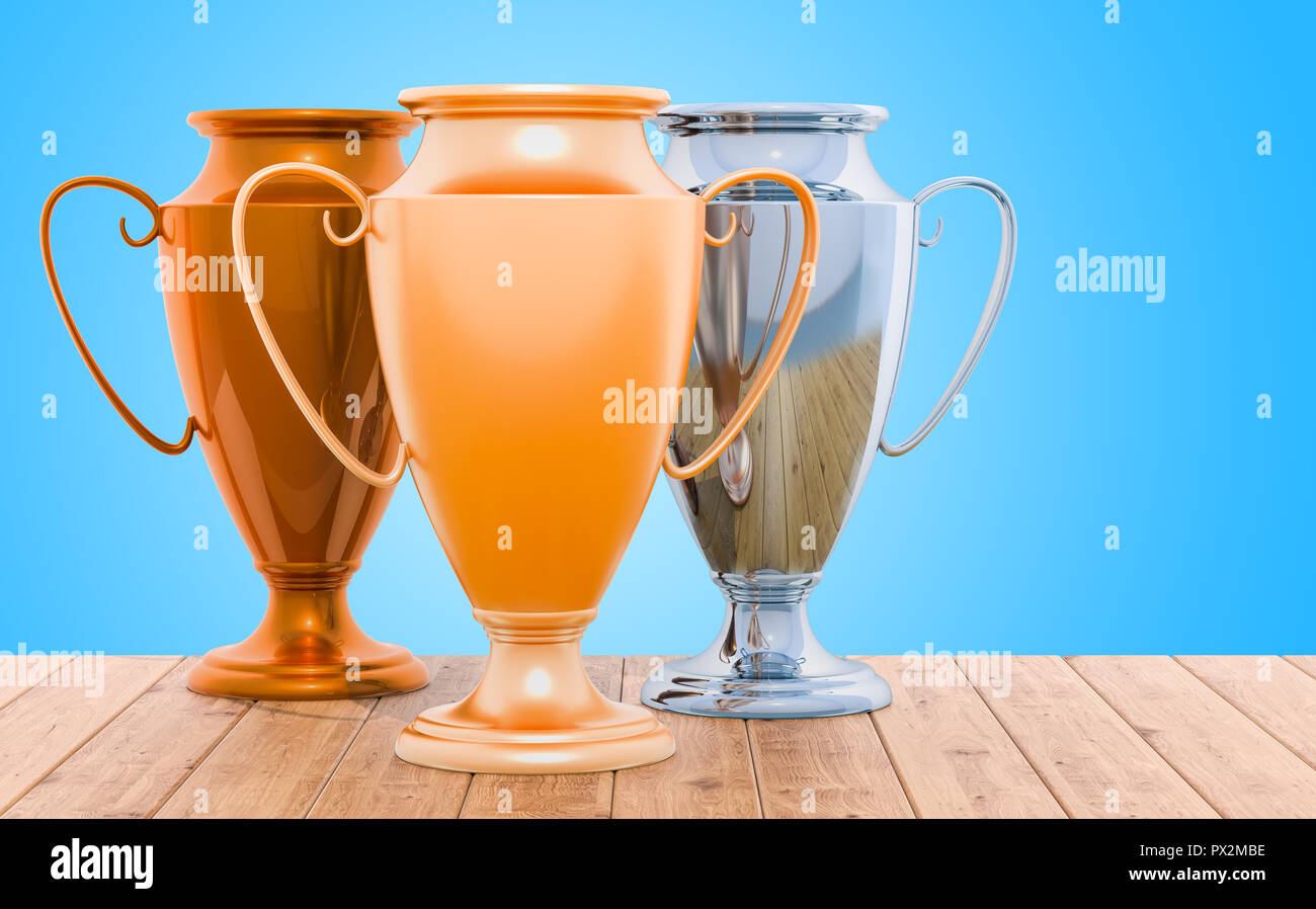 Golden, silver and bronze trophy cups on the wooden table, 3D rendering - Stock Image