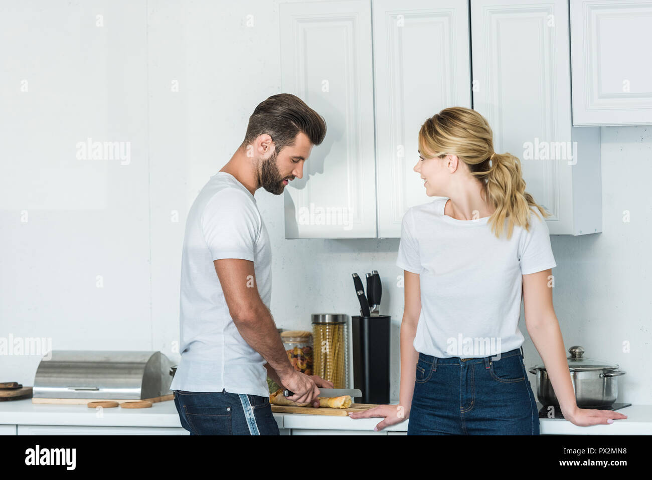 beautiful young woman looking at boyfriend cutting baguette in kitchen - Stock Image