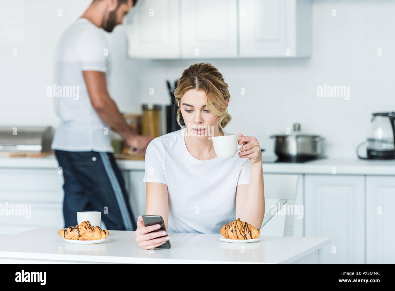 young woman drinking coffee and using smartphone while boyfriend cooking breakfast behind - Stock Image